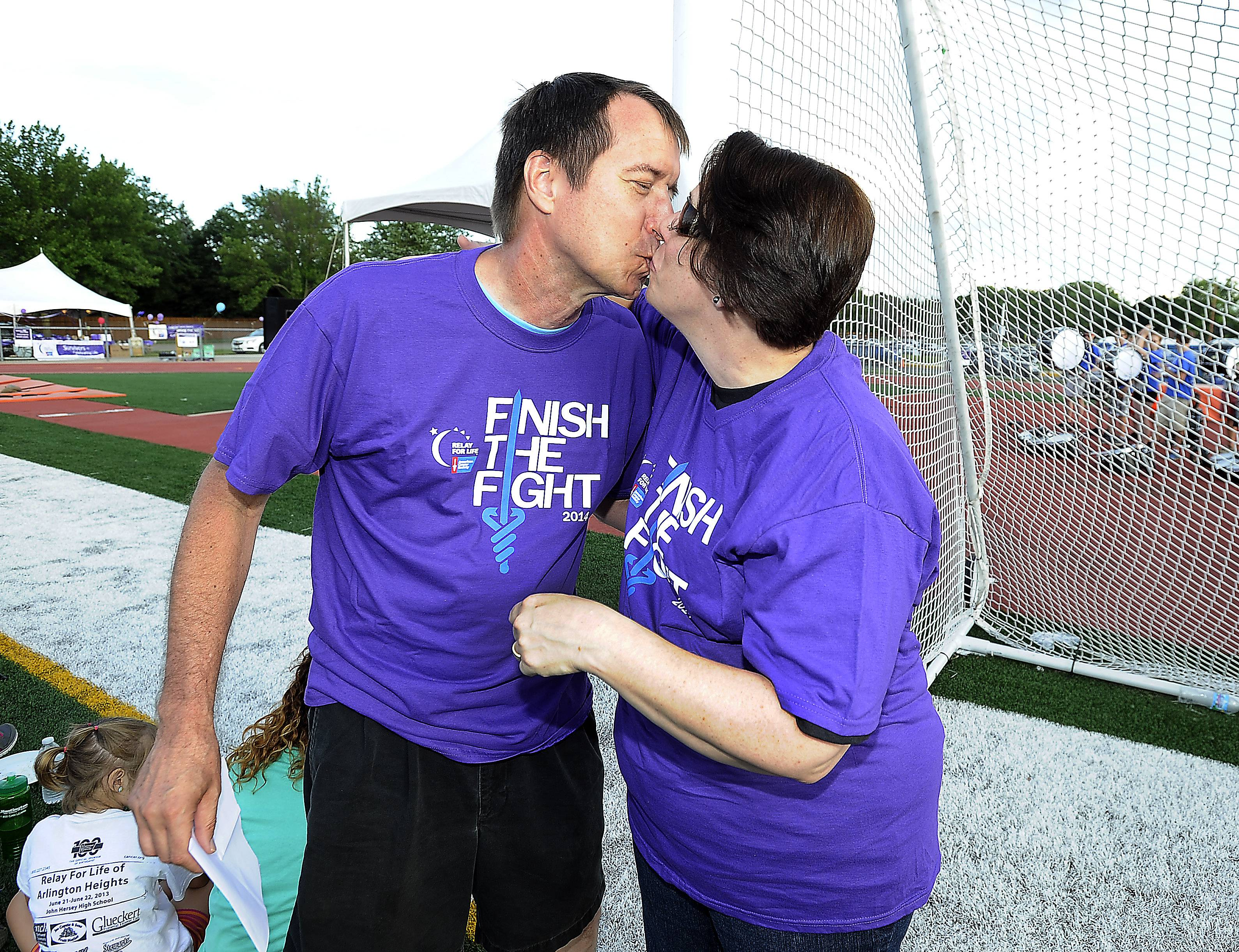 Breast cancer survivor Cheryl Tyrcha of Mount Prospect kisses her husband, Ed, in thanks for his support Friday at the American Cancer Society Relay For Life at John Hersey High School in Arlington Heights. Ed is also a cancer survivor, as his  kidney cancer has been in remission for over a year. Cheryl has been in remission  for more than seven years.