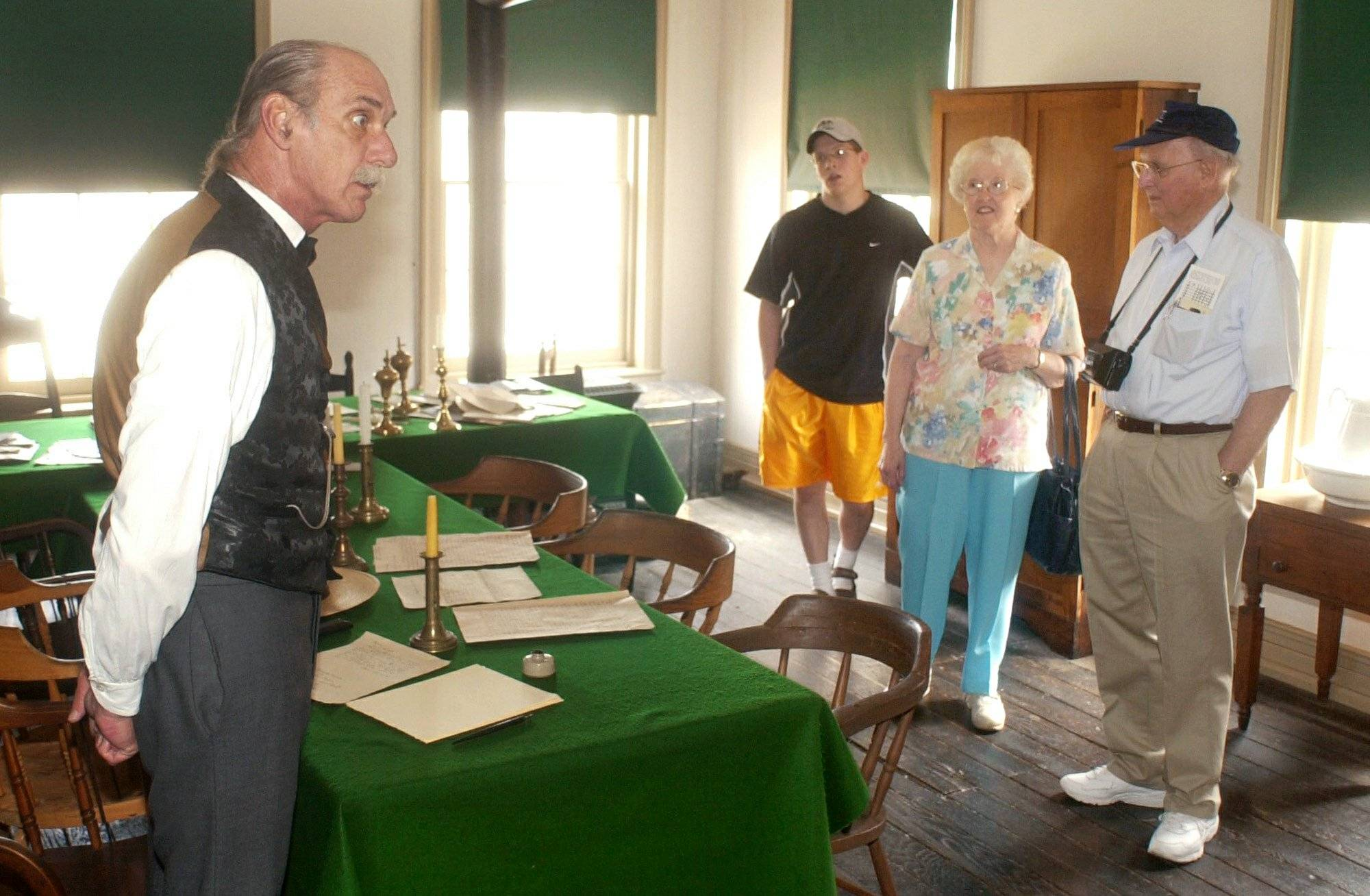 Bill Sherer, left, a historic site interpreter for the Lincoln-Herndon Law Offices in Springfield, portrays Gibson Harris, a law clerk of Lincoln's for a group of tourists.