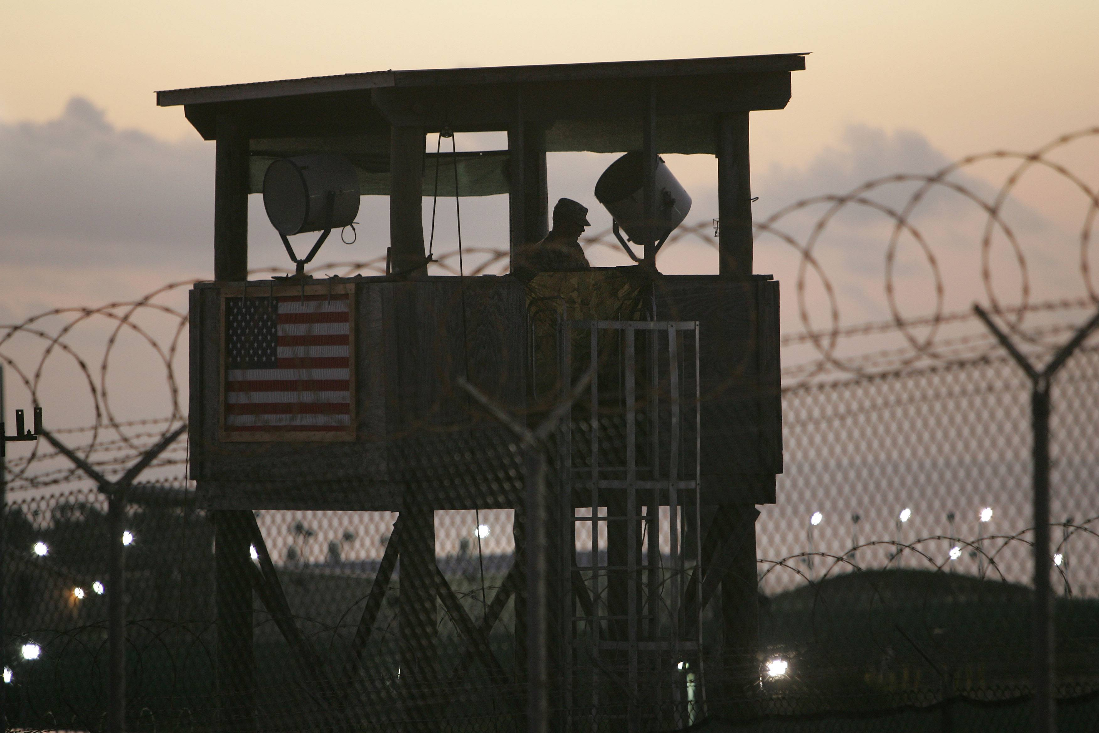 A U.S. soldier keeps watch from a guard tower overlooking Camp Delta detention center on Guantanamo Bay U.S. Naval Base in Cuba. The defense bill bars 85 percent of the funds in the account for overseas conflicts until Defense Secretary Chuck Hagel reassures lawmakers that congressional notification on Guantanamo transfers will be respected.