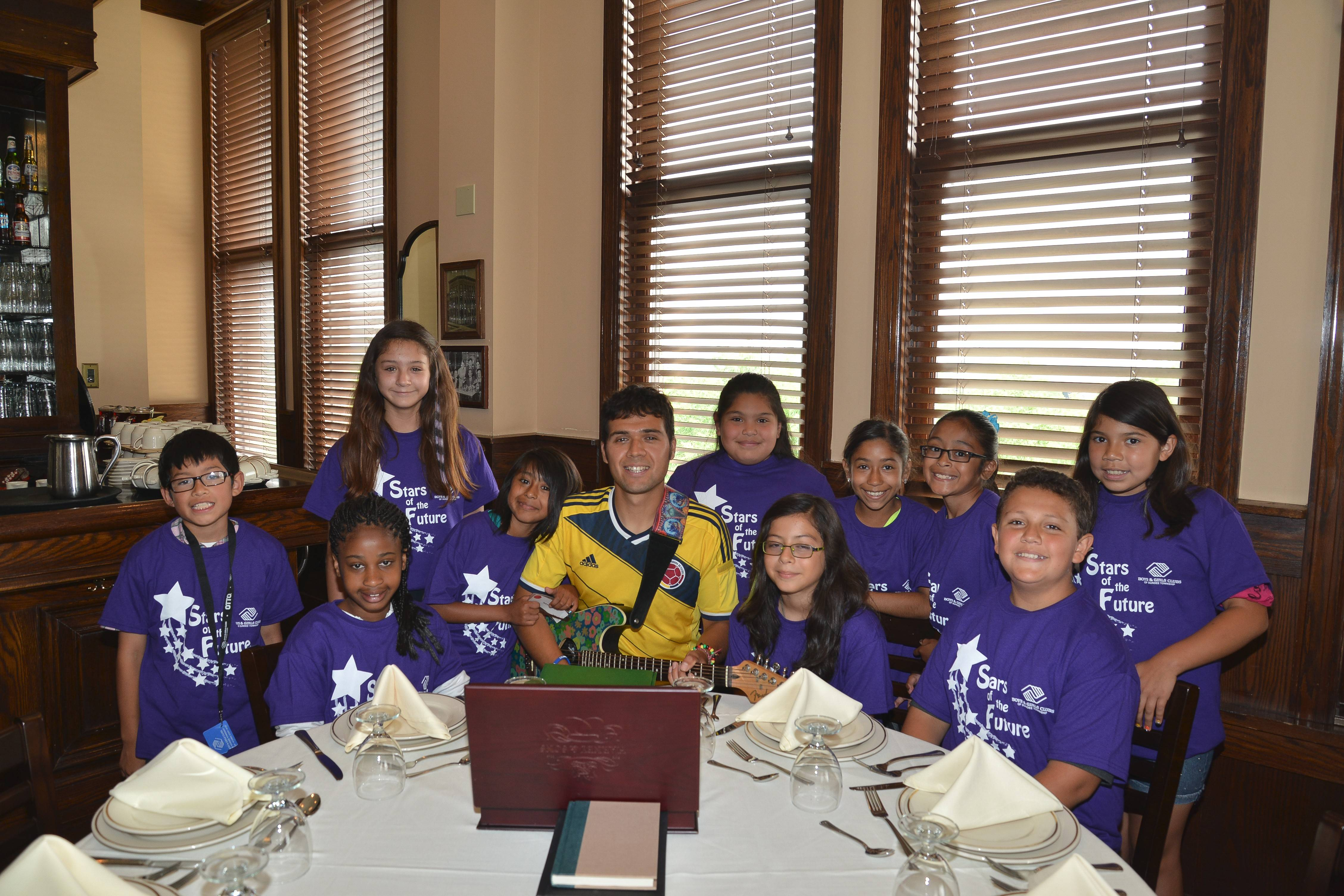 C.J. Solarte, choir director for the Boys and Girls Club of Dundee Township, with his elementary age choir at the United Way luncheon June 19. The youngsters opened the luncheon with The Star-Spangled Banner, followed by two other numbers.