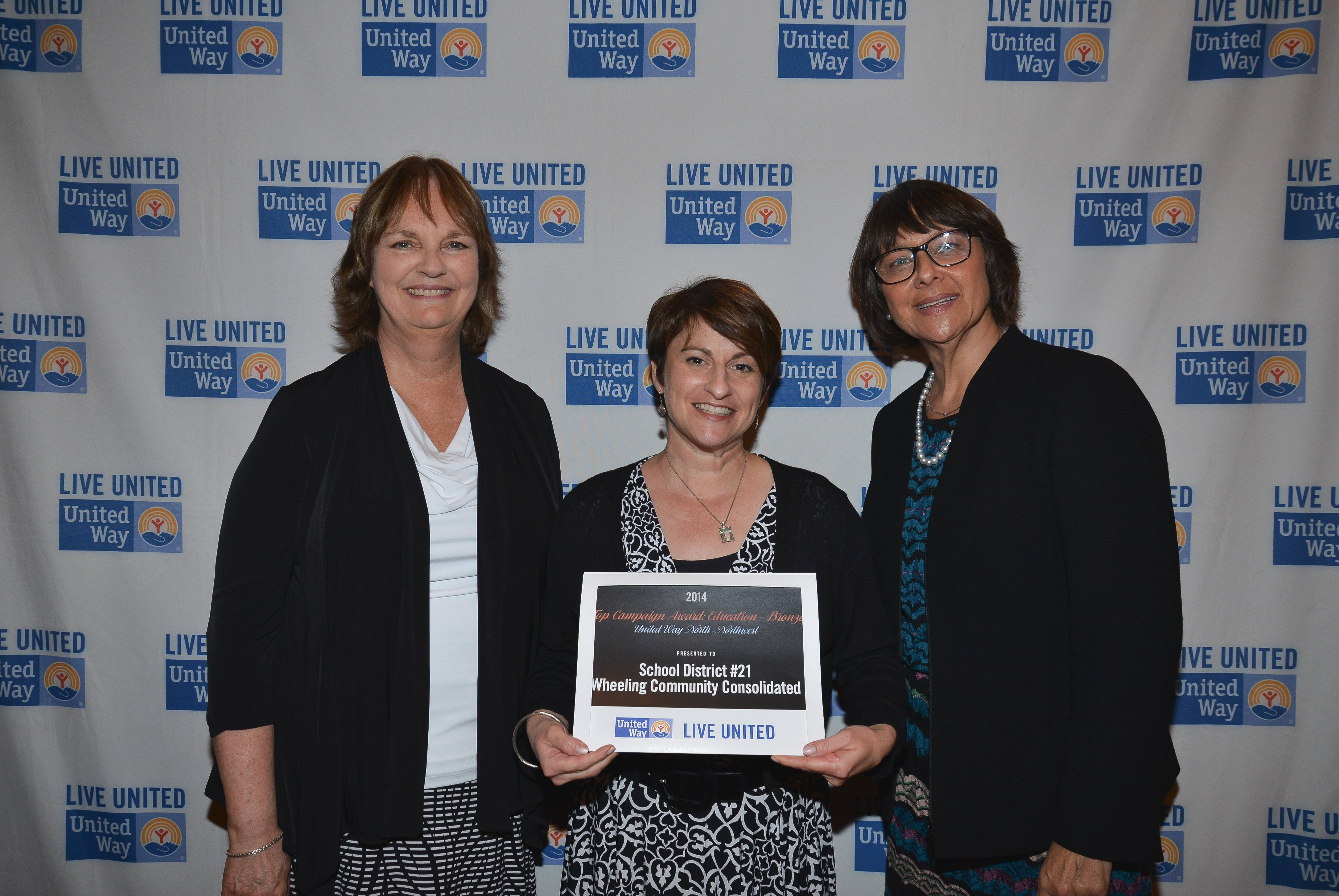 Lynn Glickman, assistant superintendent for human resources in Wheeling Township District 21, accepts her district's award, flanked by Marcia McMahon, left and Deborah Price.
