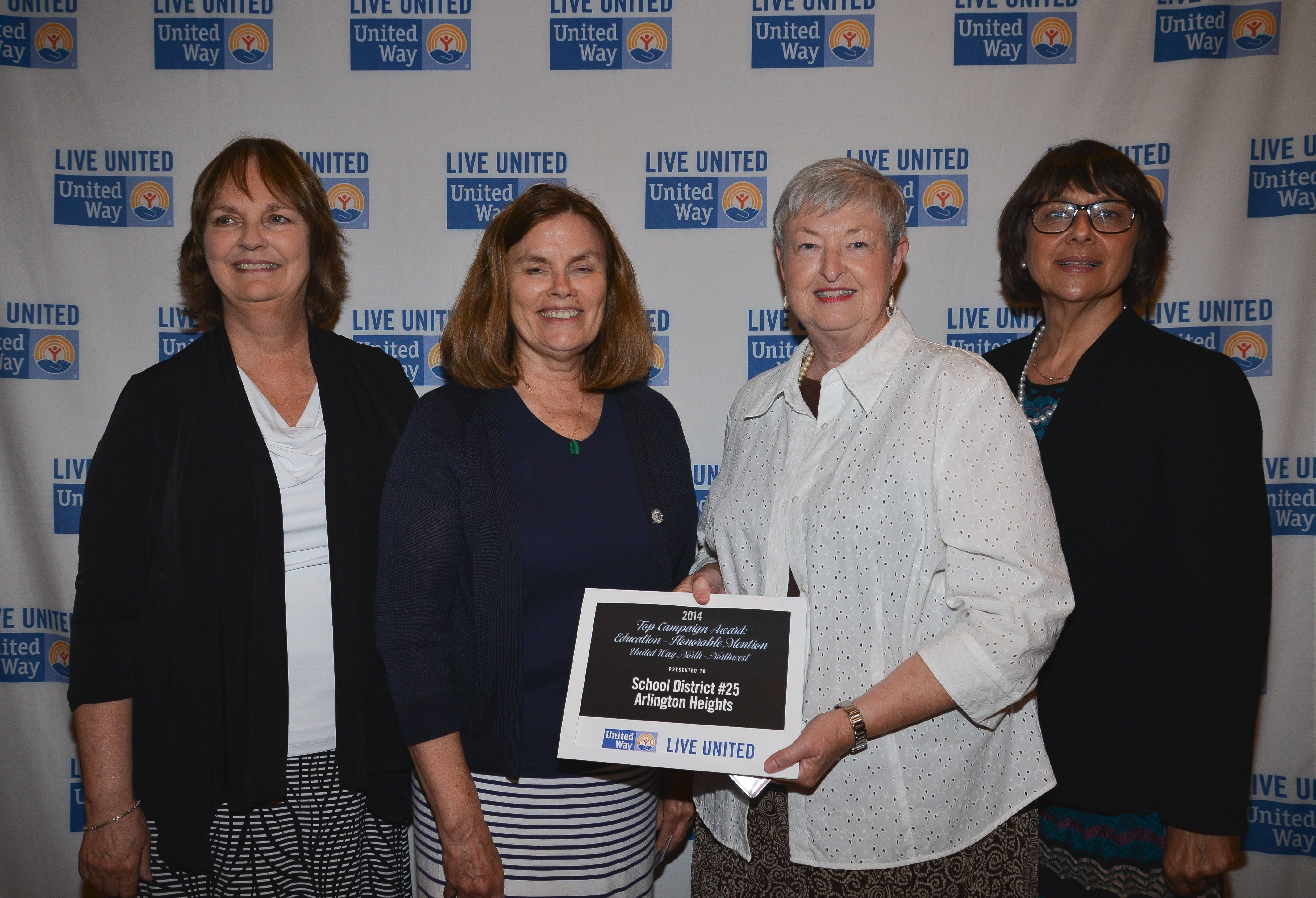 Sarah Jerome, retiring superintendent of Arlington Heights District 25 (in white), and Debra Williams, administrative assistant to the superintendent, pose with their award, flanked by Marcia McMahon, far left, and Deborah Price, far right.