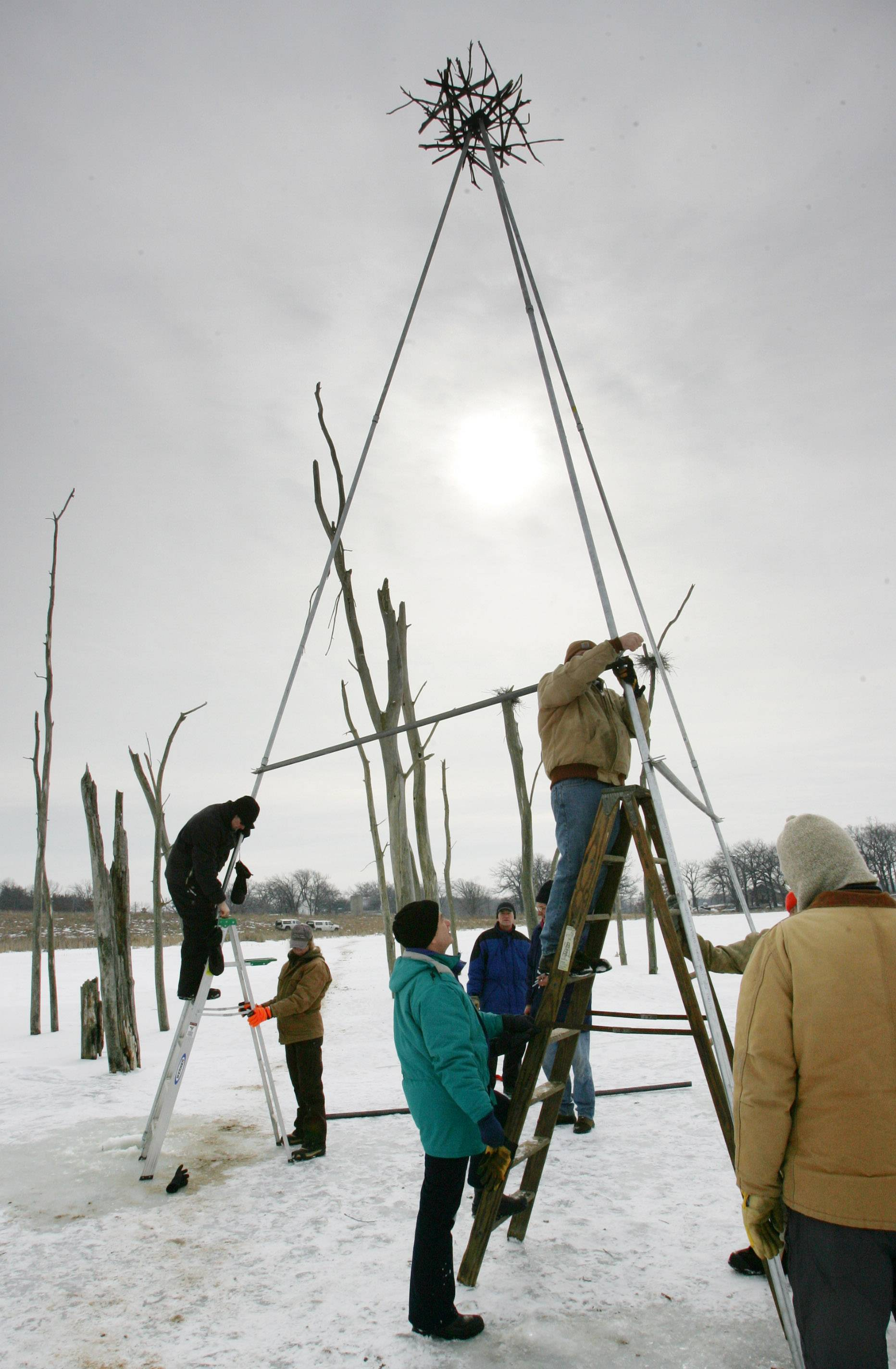 Elliot Bennett of Evanston, left, and Greg Zink of Mundelein work on a frame for the heron nesting platforms in 2010 at the Almond Marsh Forest Preserve in Libertyville Township. The 11 new platforms will help the heron population continue in the marsh.