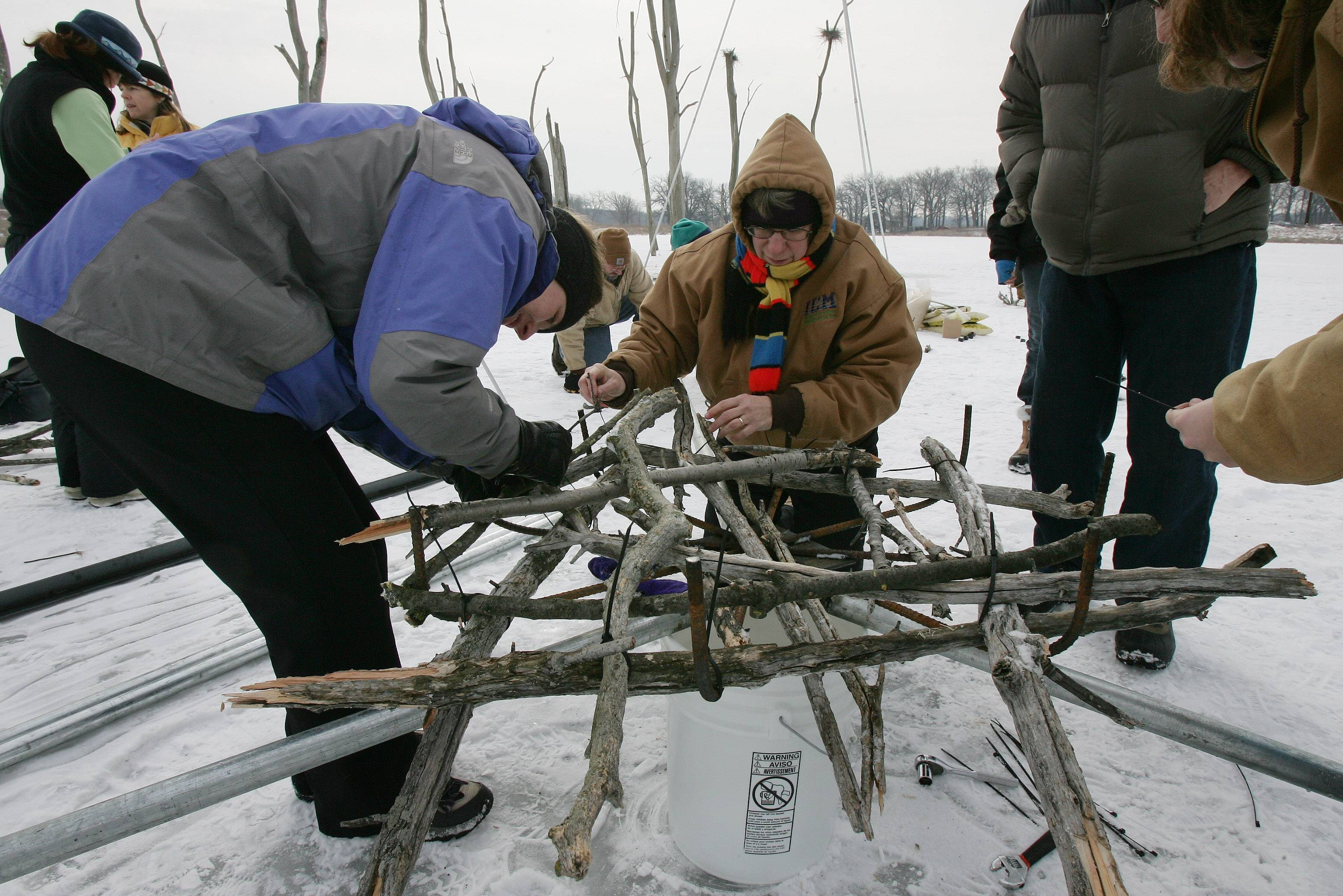 Giselle Bethke of Wilmette, left, and Sandy Kubillus of Waukegan tie loose sticks together to make a nest frame as volunteers and members of the Lake County Forest Preserve and the Lake County Audubon Society install great blue heron nesting platforms in 2010.