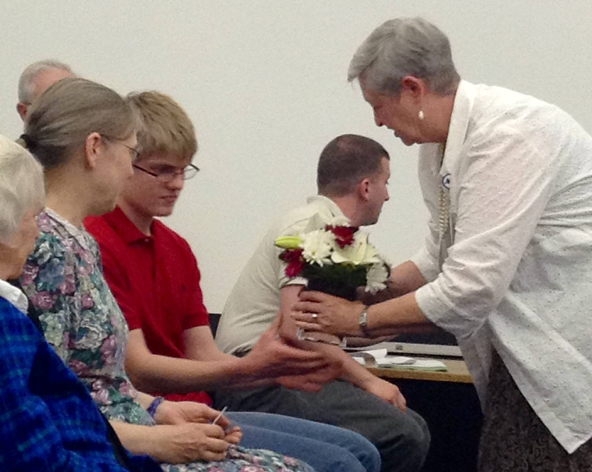 District 25 Superintendent Sarah Jerome presents flowers and the name card for board member Phil Crusius' seat to his wife, Patty, and son, Daniel, at Thursday's meeting. Crusius died of cancer earlier this month.