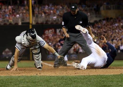 Minnesota Twins' Eduardo Escobar, right, beats the tag by White Sox catcher Adrian Nieto to score the winning run on a walk off single by Brian Dozier Friday. The Twins won 5-4.