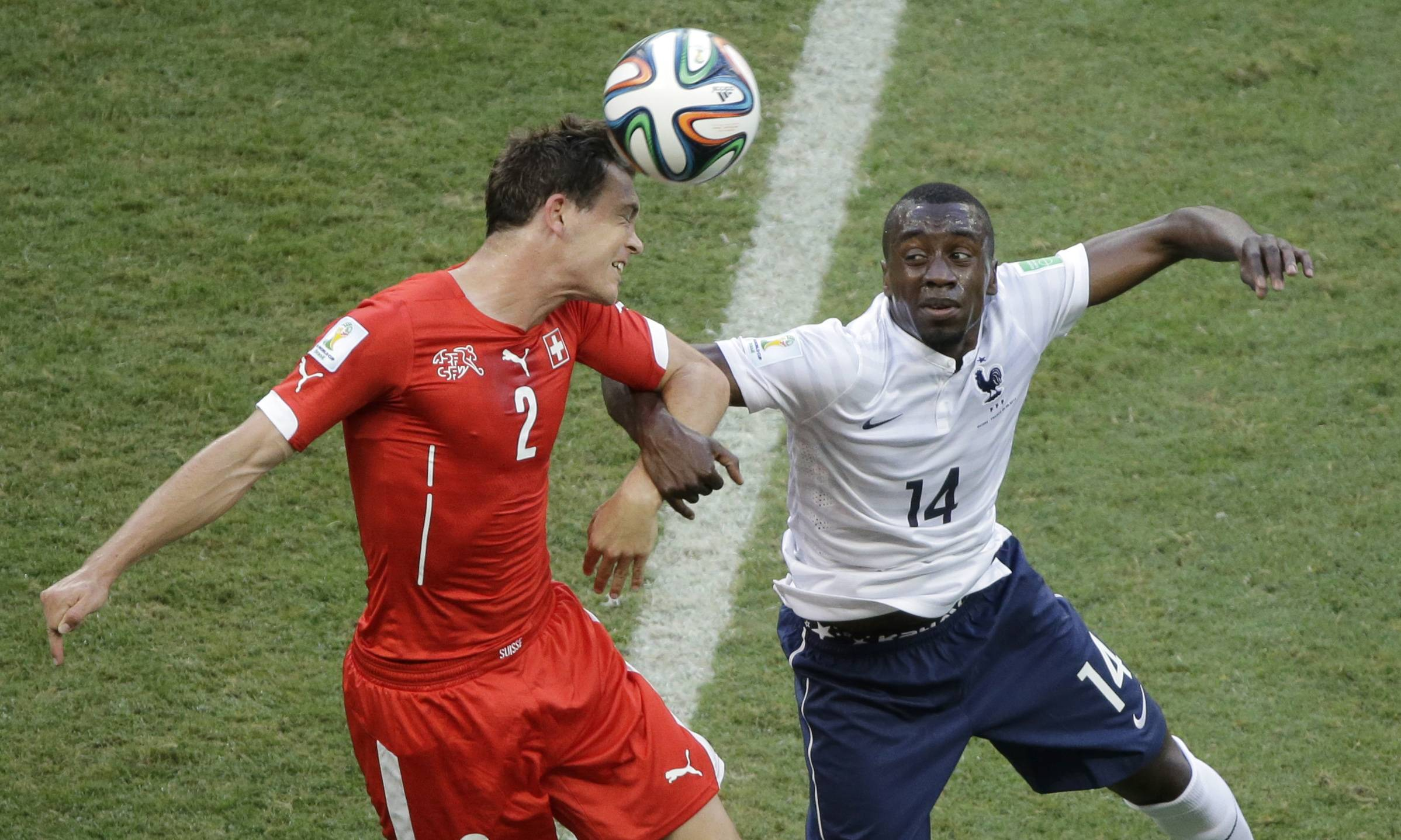 Switzerland's Stephan Lichtsteiner, left, and France's Blaise Matuidi go for a header during the group E World Cup soccer match between Switzerland and France at the Arena Fonte Nova in Salvador, Brazil, Friday, June 20, 2014.