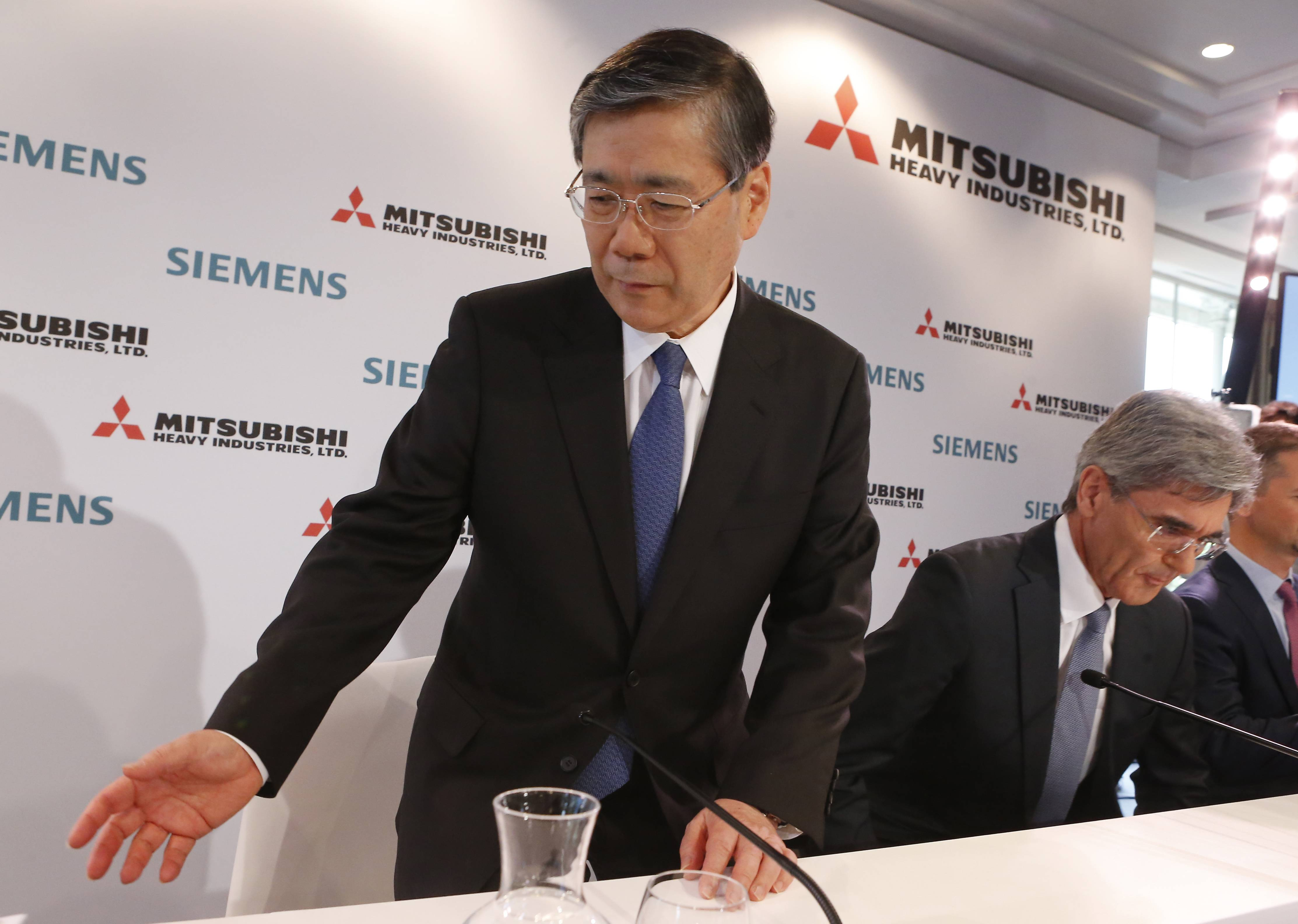 Siemens CEO Joe Kaeser, right, and Mitsubishi CEO Shunichi Miyanaga, arrive Tuesday for their press conference in Paris. The CEOs from Siemens and Mitsubishi Heavy Industries met with the French president to promote their joint offer to buy parts French engineering company Alstom and head off a rival bid from General Electric Co.