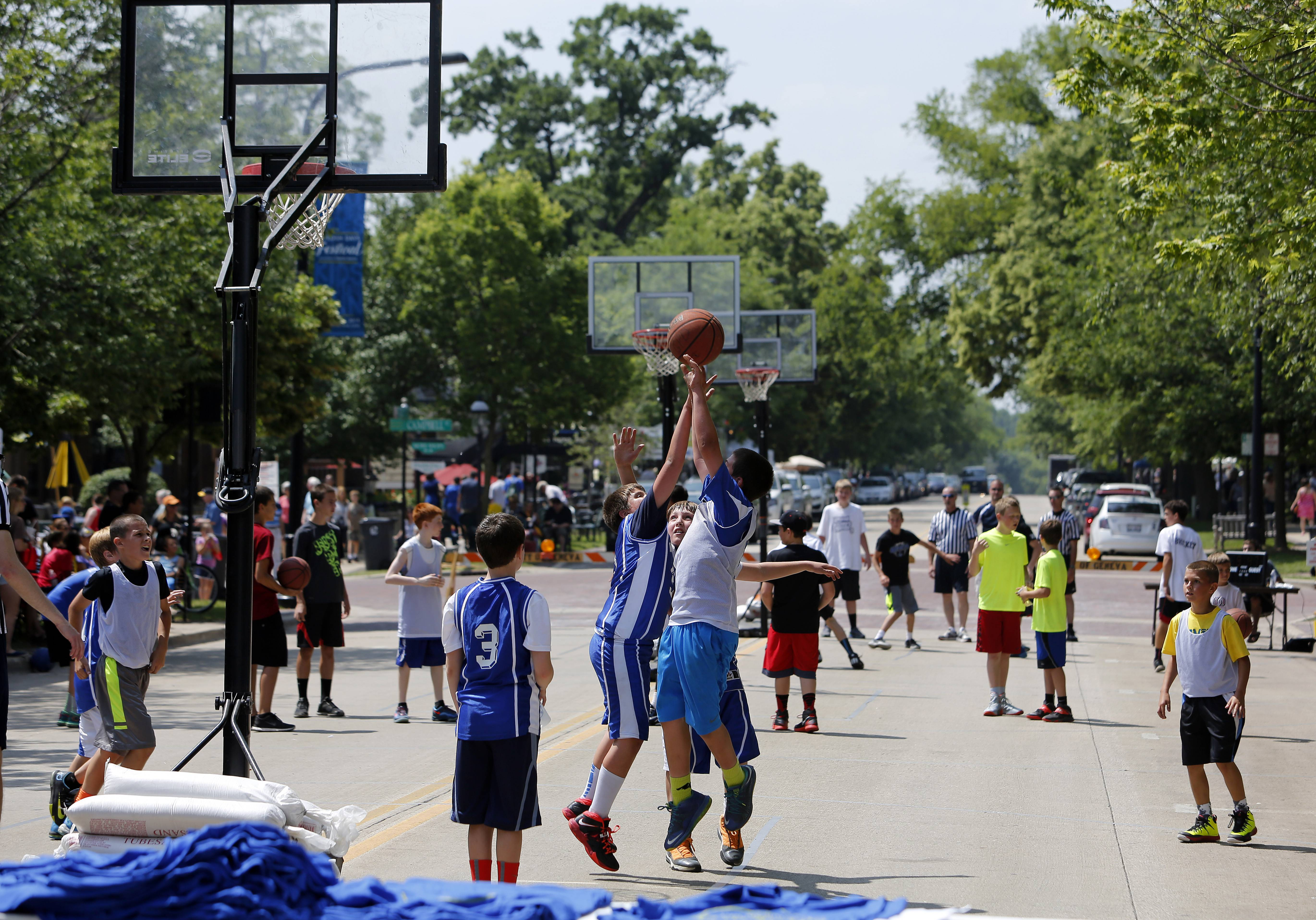 Joey Pupillo, 11, of Addison tries to block a shot by Mason Mascari, 11, of Geneva in the 3 on 3 basketball tournament on Third Street during the 65th Geneva Swedish Days Saturday in downtown Geneva.