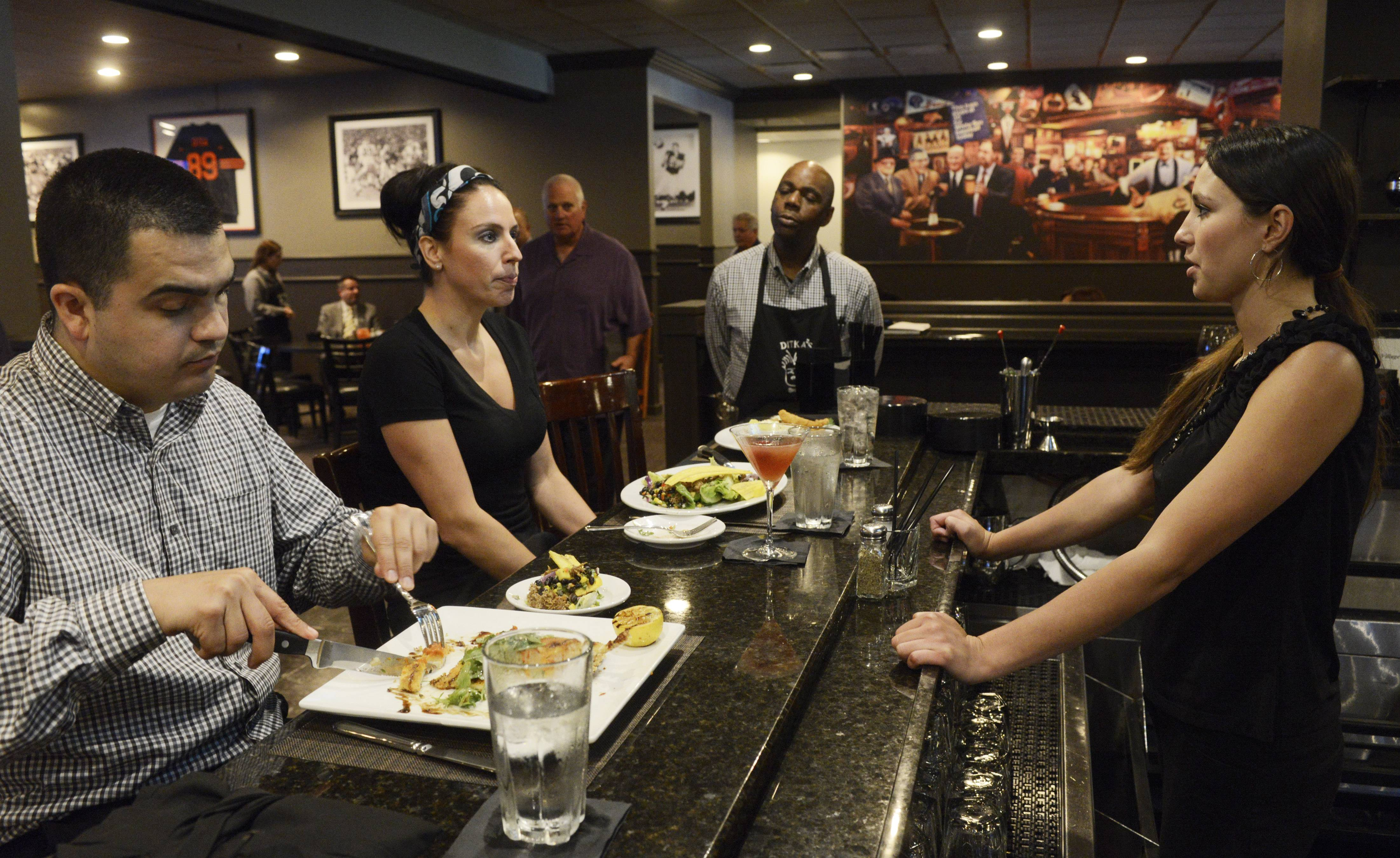Bartender Haely Jorgensen, right, chats with Andy Lopez and Nicole Szwed, Ditka's employees, as they sample the food.