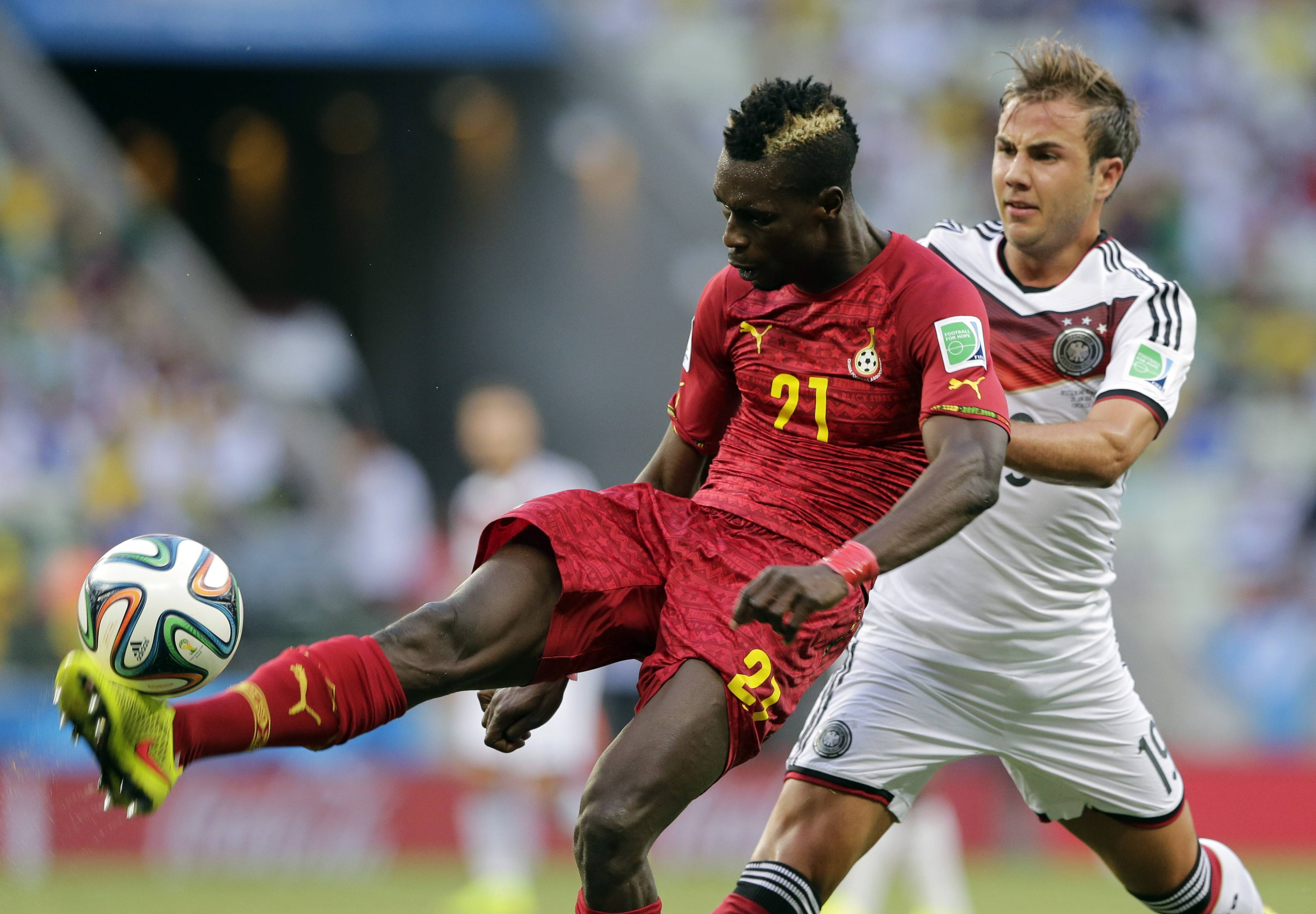 Ghana's John Boye, left, clears the ball from Germany's Mario Goetze during the group G World Cup soccer match at the Arena Castelao in Fortaleza, Brazil, Saturday, June 21, 2014. (AP Photo/Matthias Schrader)