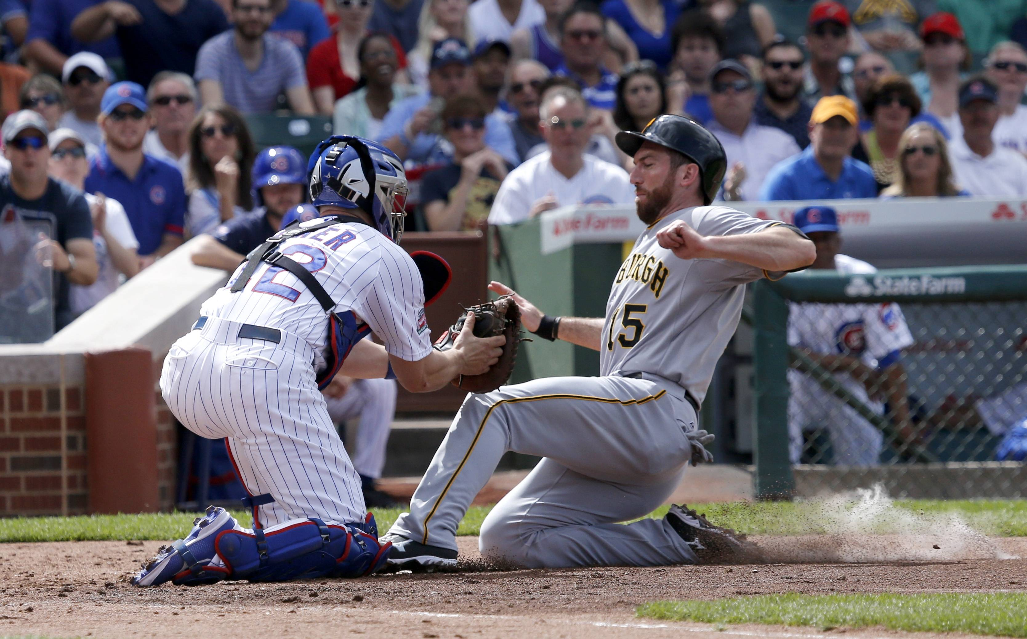 Chicago Cubs catcher John Baker, left, tags out Pittsburgh Pirates' Ike Davis at home plate during the second inning of Friday's win over the Pirates. The play was upheld on video review.