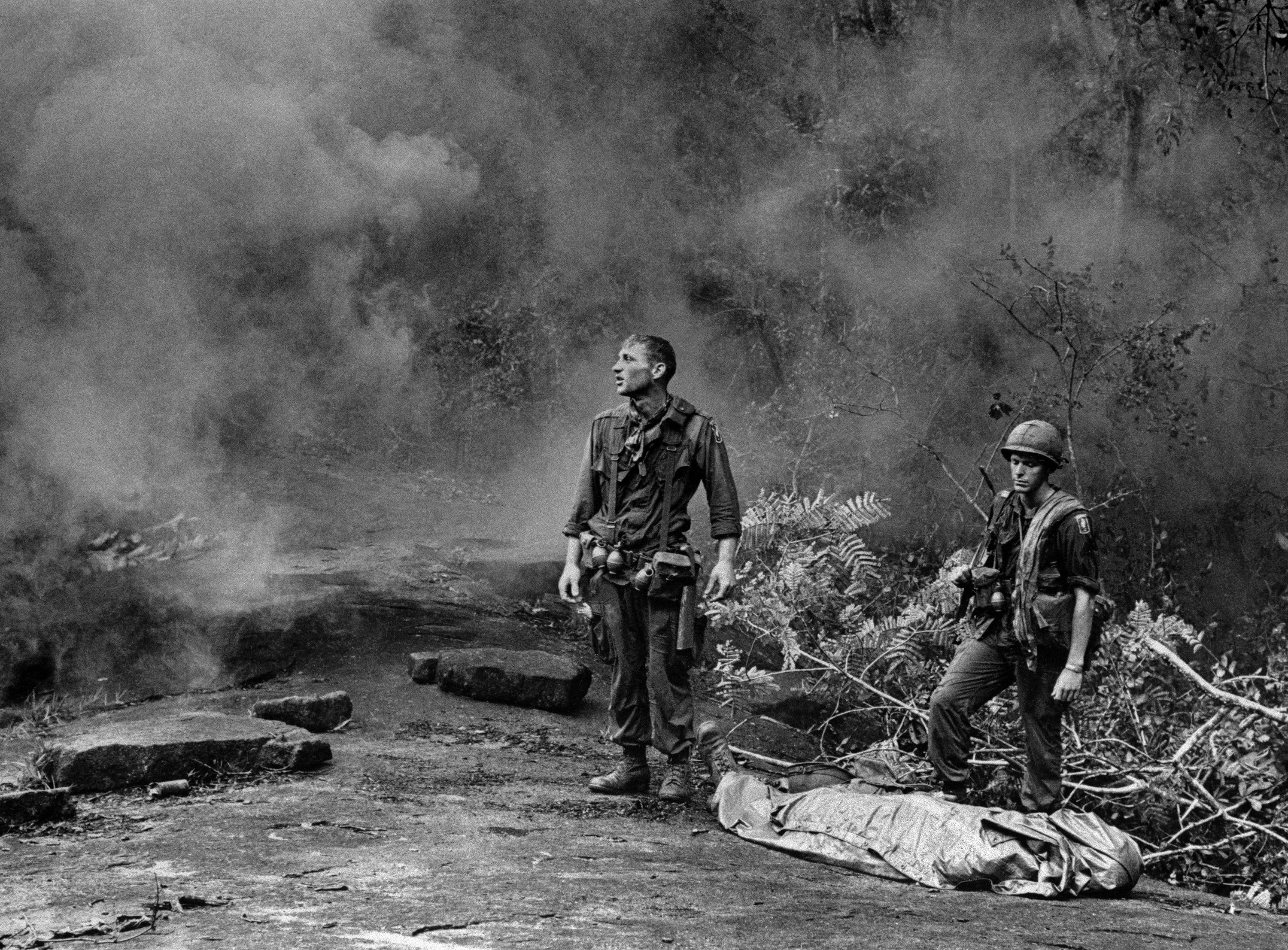 "U.S. Army soldier Ruediger Richter gazes aloft as a helicopter prepares to land to pick up the body of a fallen soldier killed by mortar fire in South Vietnam. Taken by an Army photographer and transmitted worldwide by The Associated Press, the image came to be known widely as ""The Agony of War."""
