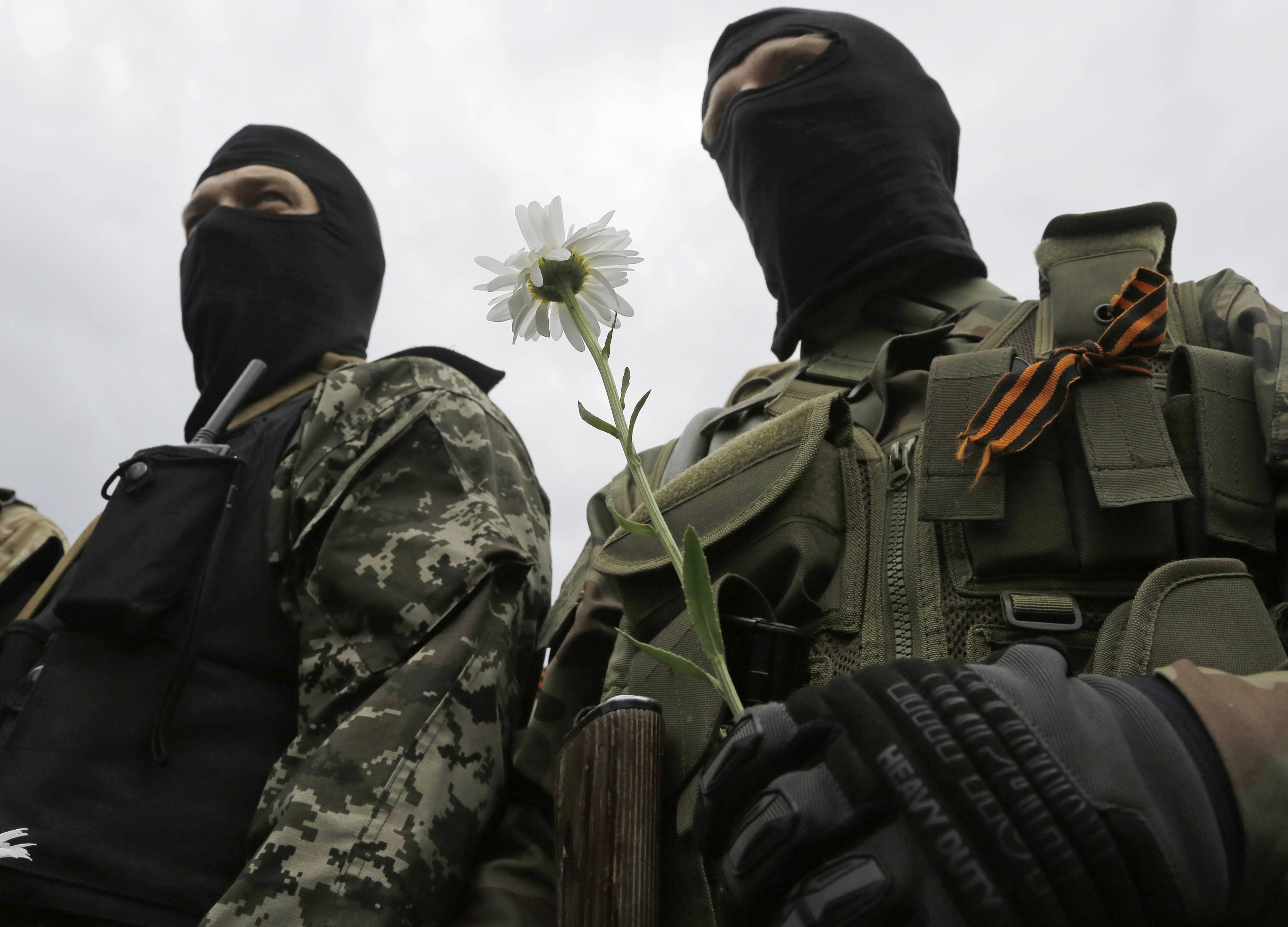 A pro-Russian fighter holds a flower Saturday after taking an oath in Donetsk, eastern Ukraine. Ukrainian President Petro Poroshenko ordered his forces to cease-fire Friday and halt military operations for a week.