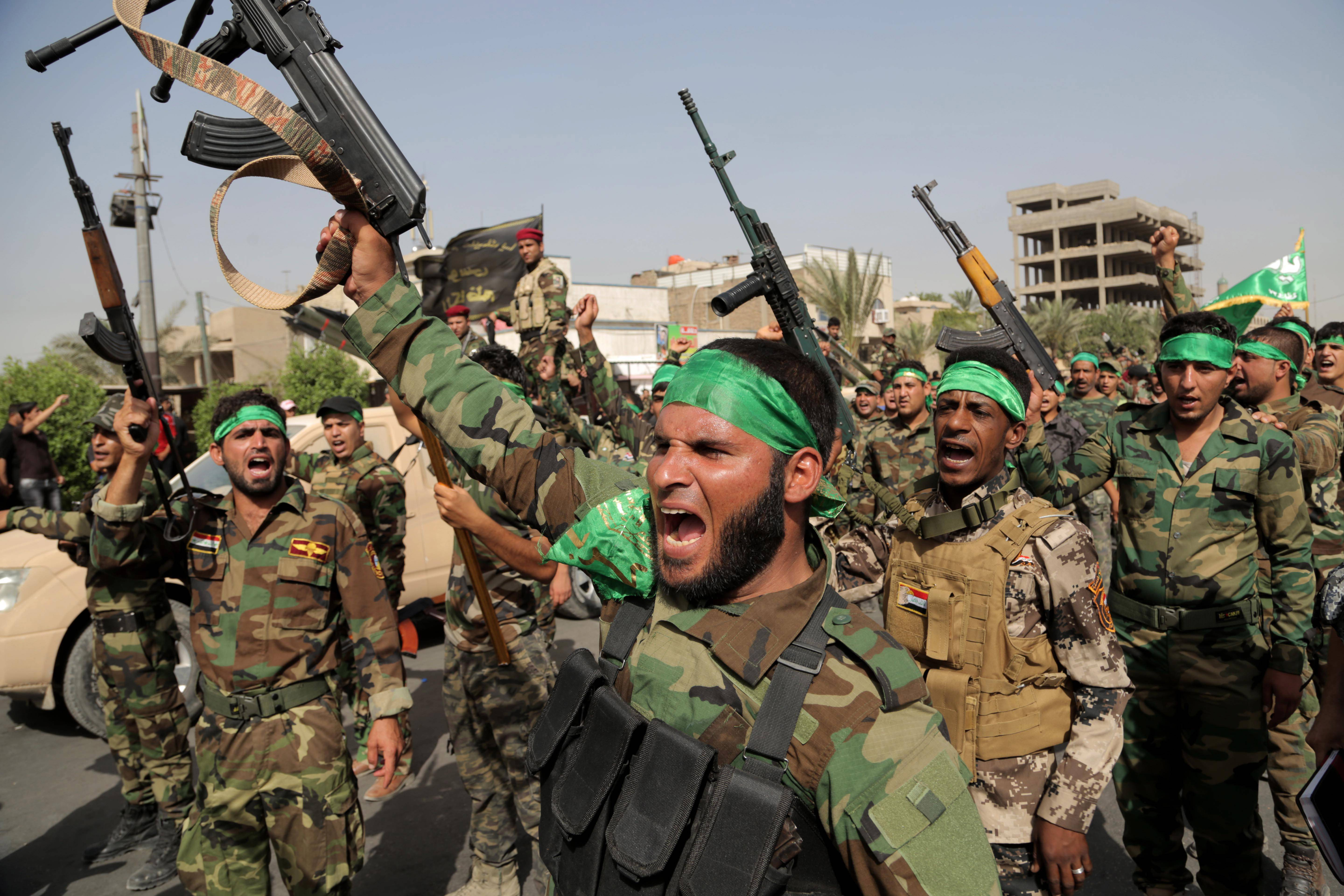 "Volunteers in the newly formed ""Peace Brigades"" raise their weapons Saturday and chant slogans against the al-Qaida-inspired Islamic State of Iraq and the Levant during a parade in the Shiite stronghold of Sadr City, Baghdad."