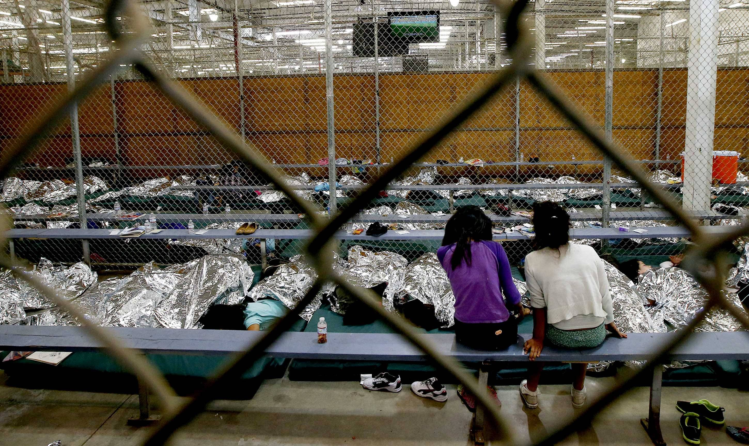 Two young girls watch a World Cup soccer match Wednesday on a television from their holding area where hundreds of mostly Central American immigrant children are being processed and held at the U.S. Customs and Border Protection Nogales Placement Center Nogales, Ariz.