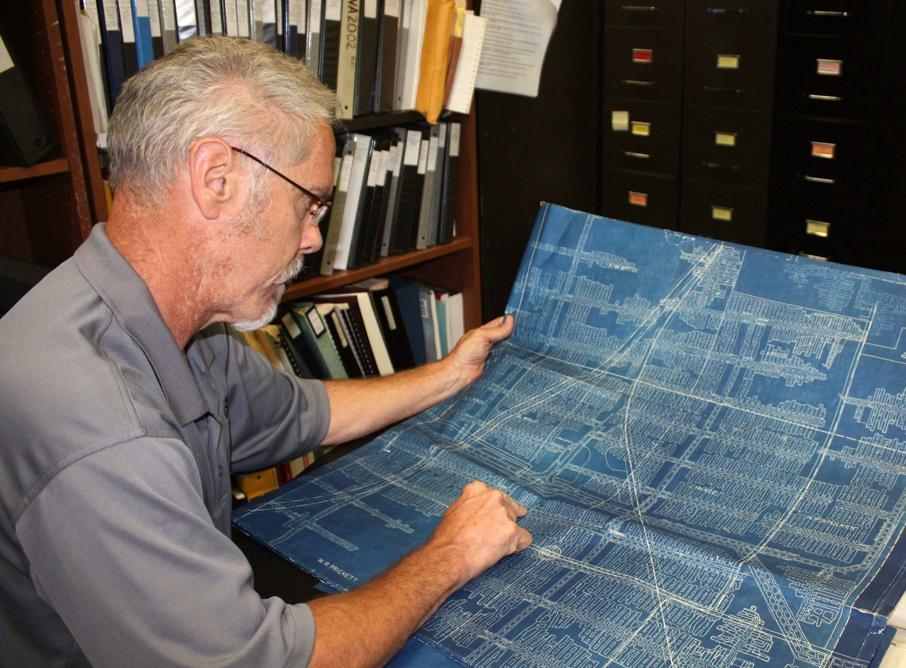 Robert Gibson, the emergency section supervisor at the DNR's Department of Mines and Minerals, looking at maps of old coal mines at Southern Illinois University Edwardsville that are being digitized by the state. Mine maps marked the locations of rooms, pillars and shafts -- necessary then and a valuable tool for state officials, homeowners and developers today because of the damage current structures can sustain if an abandoned mine begins to collapse or sag. But the DNR only has about 2,000 maps for the more than 4,000 separate mines that operated in the state, Gibson said. The state is digitizing those in its archives before they deteriorate, but also is searching for as many missing maps as possible.