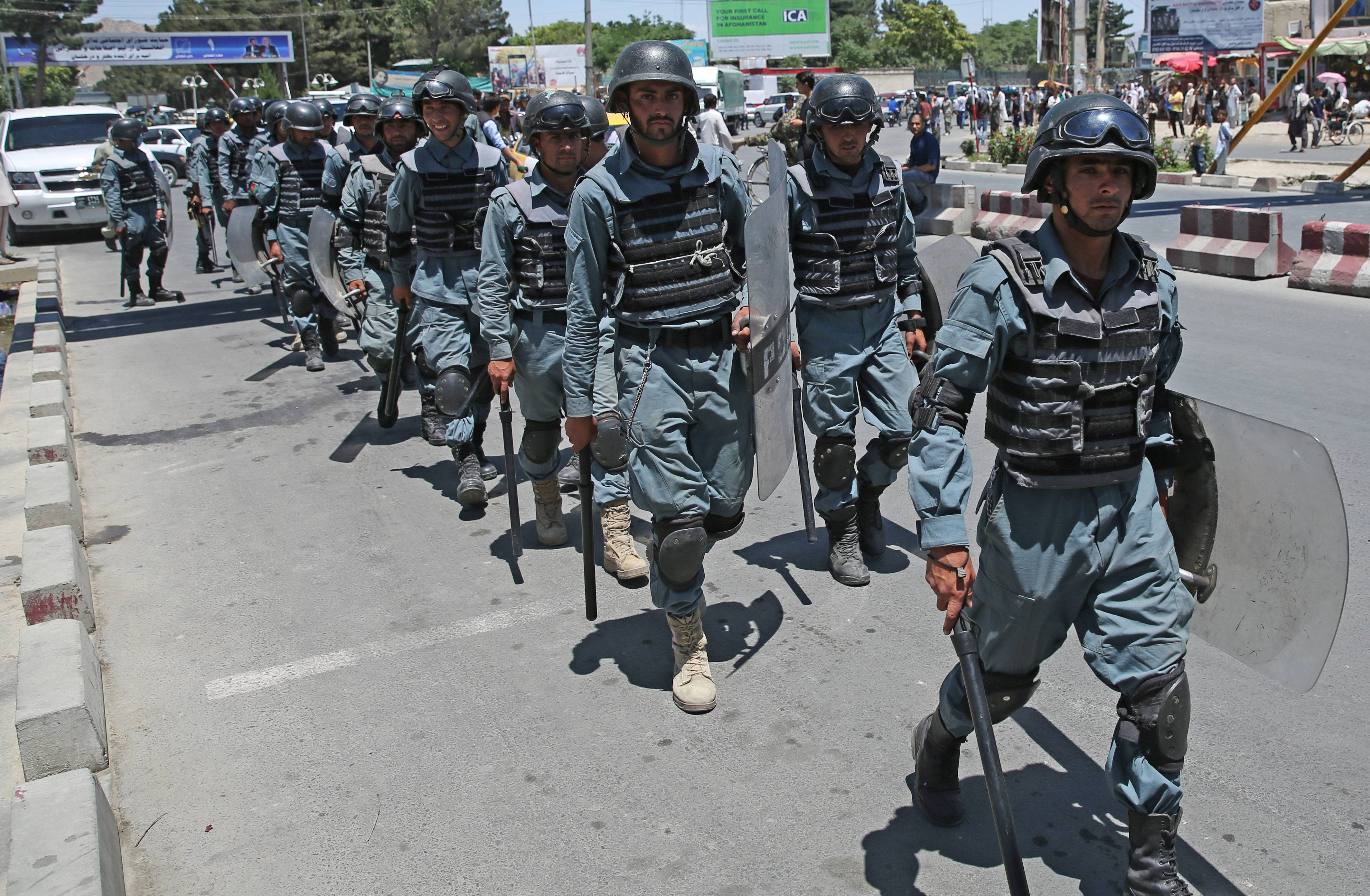 Afghanistan police forces secure an area as supporters of presidential candidate Abdullah Abdullah hold a protest in Kabul, Afghanistan, Saturday, June 21. Former Foreign Minister Abdullah, who is running against Ashraf Ghani Ahmadzai, a former finance minister, has accused electoral officials and others of trying to rig the June 14 vote against him.