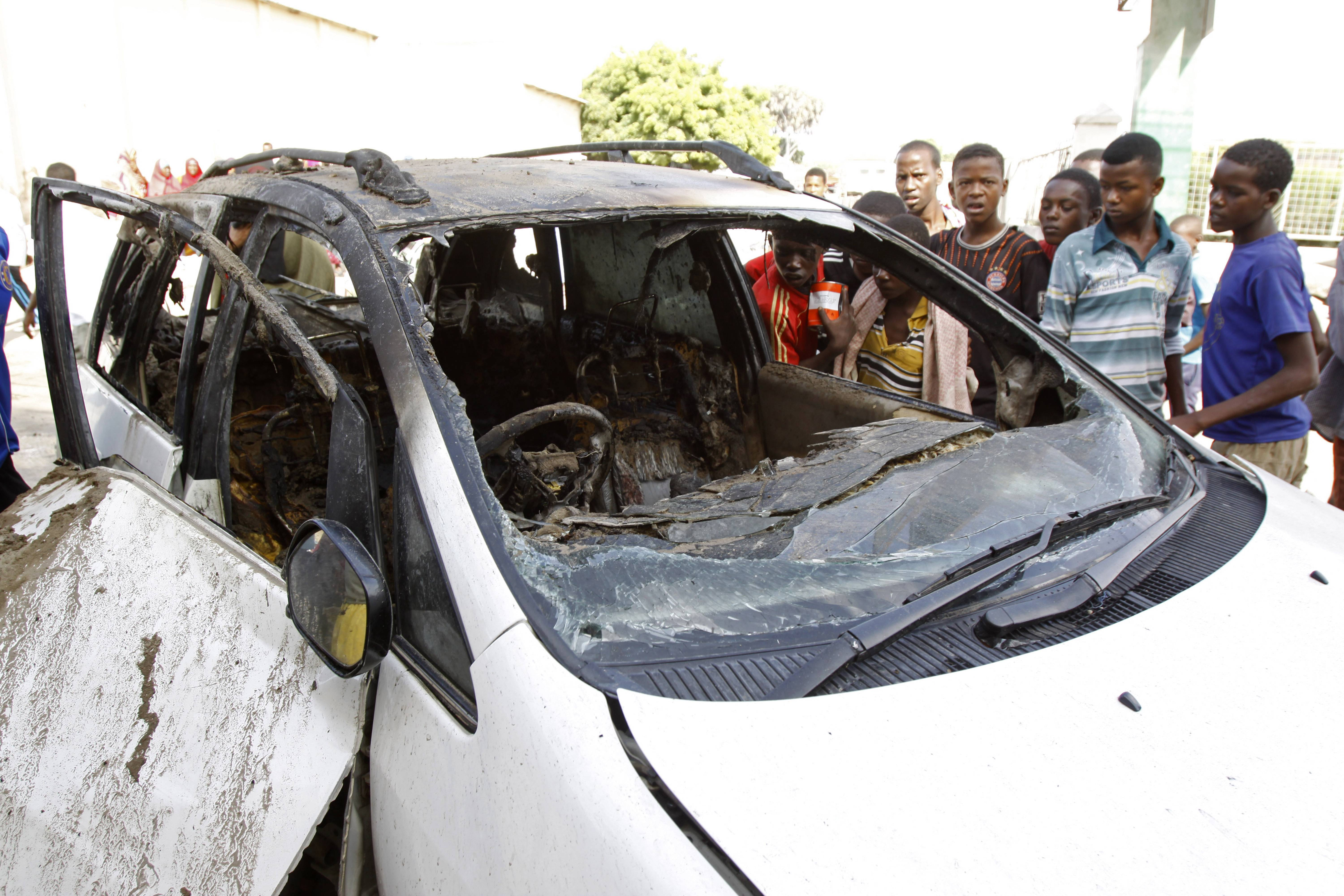 Somalis look at the smashed car in which a Somali journalist was killed by a bomb planted under his car in the Somali capital of Mogadishu, Saturday, June,  21. No group has claimed the responsibility the Assassination of Yusuf Keynan, the editor of Mustaqbal radio in Mogadishu, who died as he started his mined car to go to work in the morning, according to Abdinasir Mohamed Ali, a colleague of the murdered reporter.
