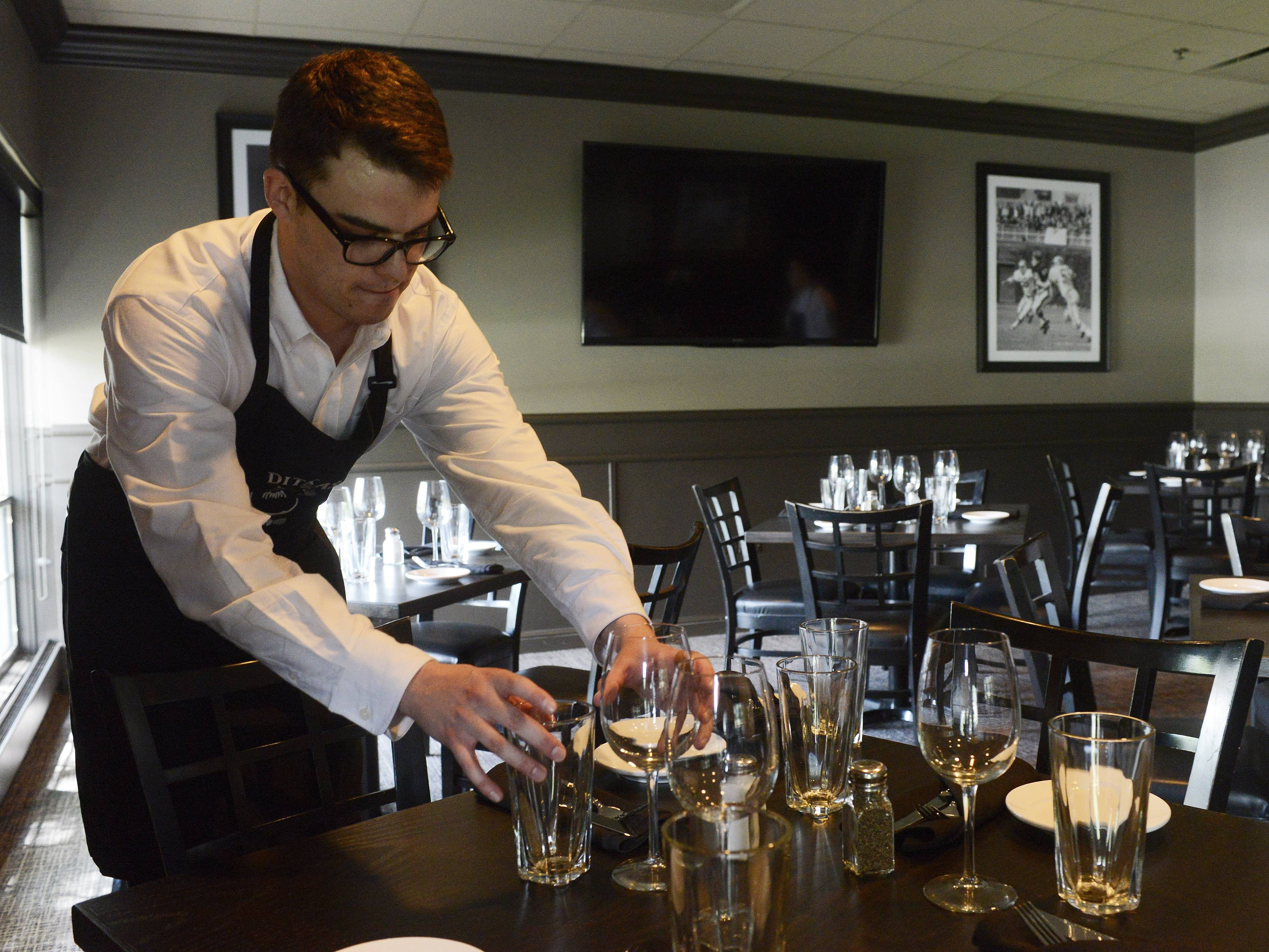 Service assistant Ed Curran sets a table at Ditka's Restaurant, which is having a private party Saturday night.