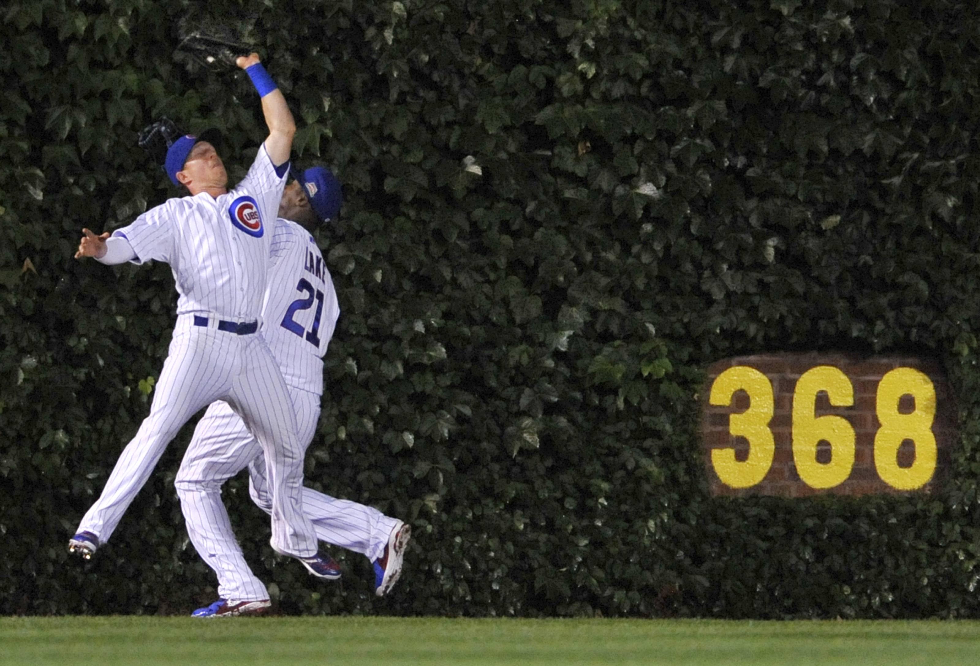 Cubs left fielder Chris Coghlan, foreground, barely misses a collision with center fielder Junior Lake while catching a flyball hit by Pittsburgh's Clint Barmes during the third inning at Wrigley Field on Saturday.