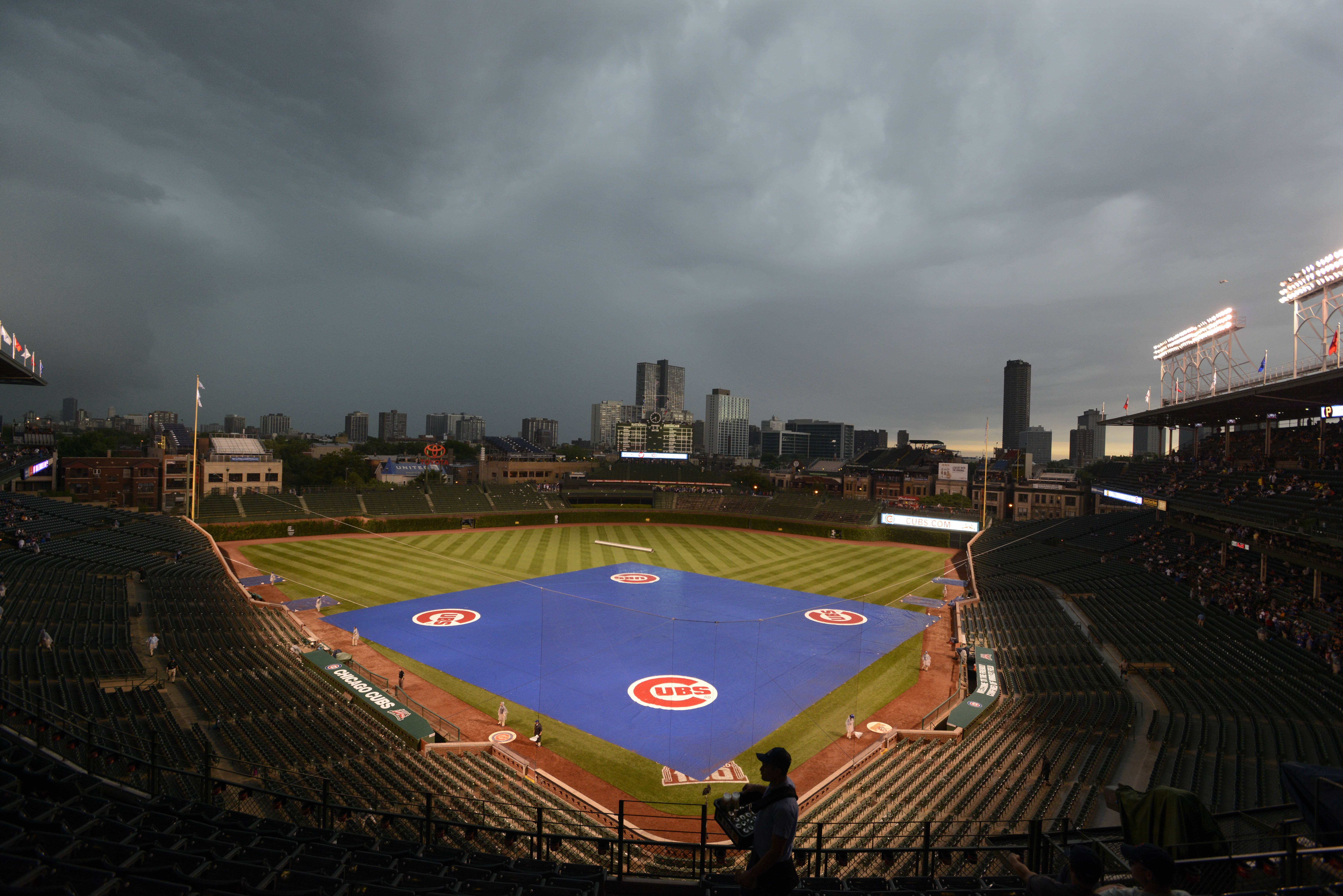 The tarp covers the infield as rain delays the start of a baseball game between the Chicago Cubs and Pittsburgh Pirates at Wrigley Field in Chicago, Saturday, June 21, 2014.