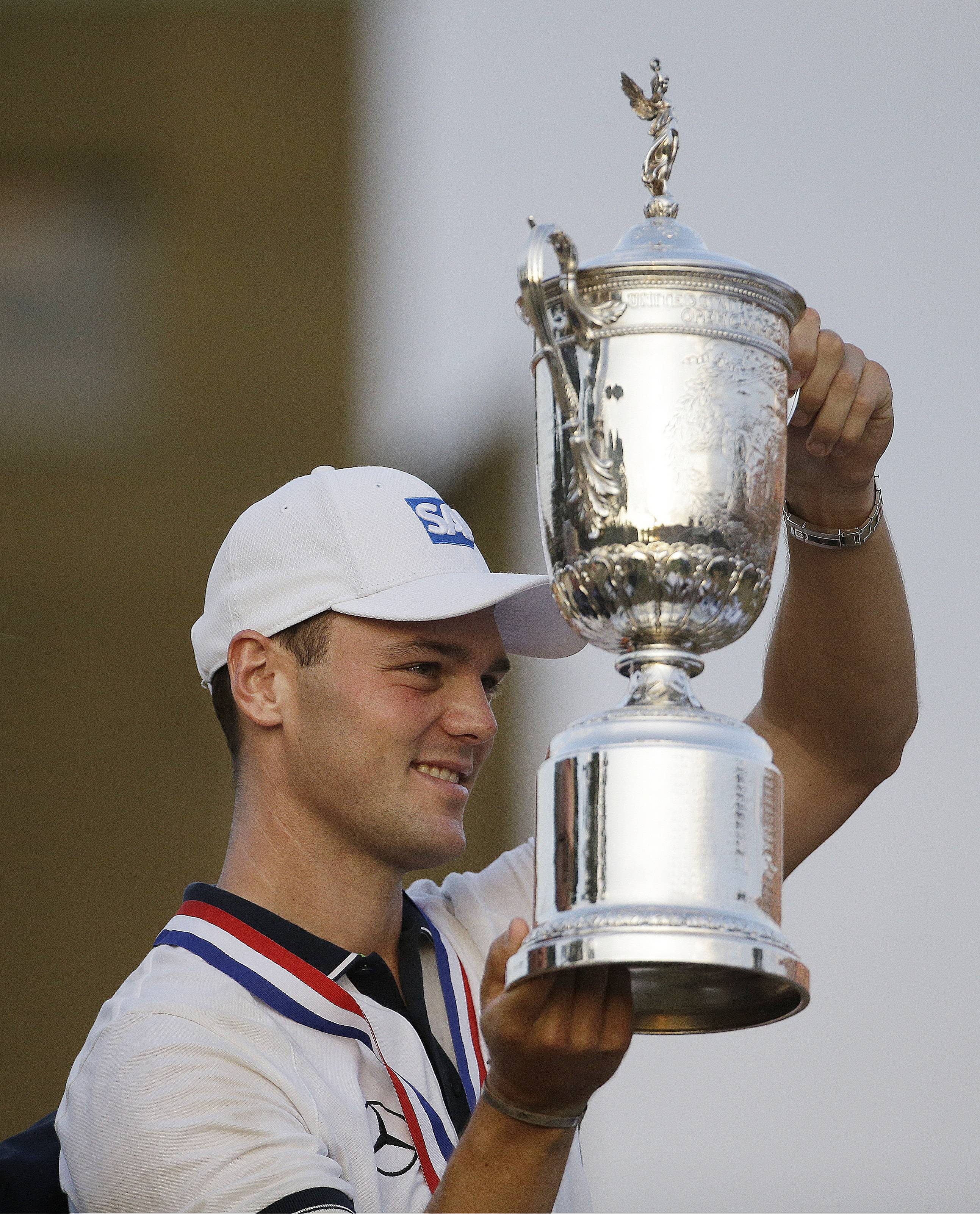 Martin Kaymer, of Germany, holds up the trophy after wining the U.S. Open golf tournament in Pinehurst, N.C., Sunday, June 15, 2014.