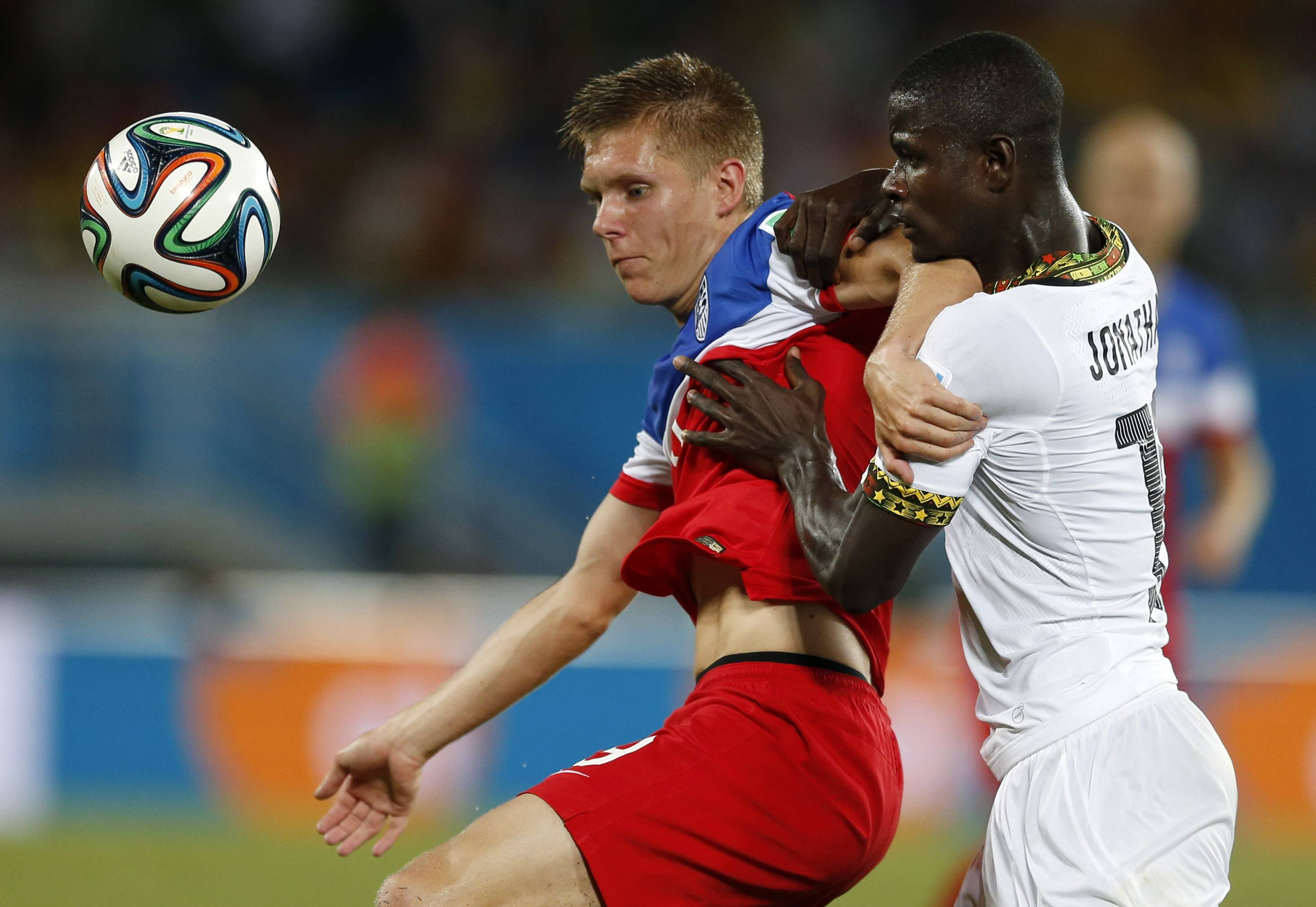 Ghana's Jonathan Mensah, right, tries to push aside United States' Aron Johannsson during the group G World Cup soccer match between Ghana and the United States at the Arena das Dunas in Natal, Brazil, Monday, June 16, 2014.