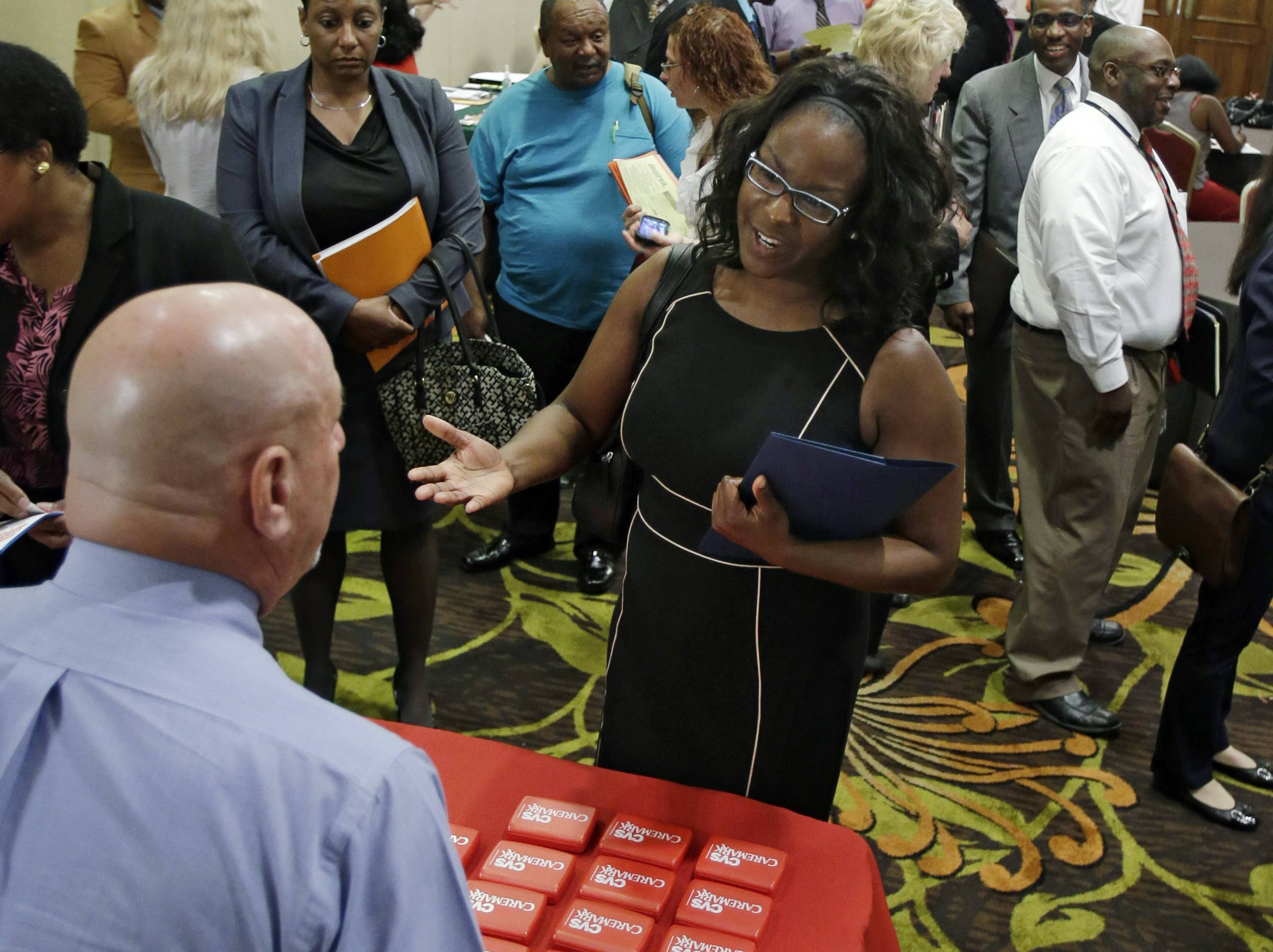 Marsha Lawson talks with a representative from CVS at the Cleveland Career Fair in Independence, Ohio. Optimism among chief executives of large U.S. companies has reached a two-year high, driven by greater optimism about hiring and sales.