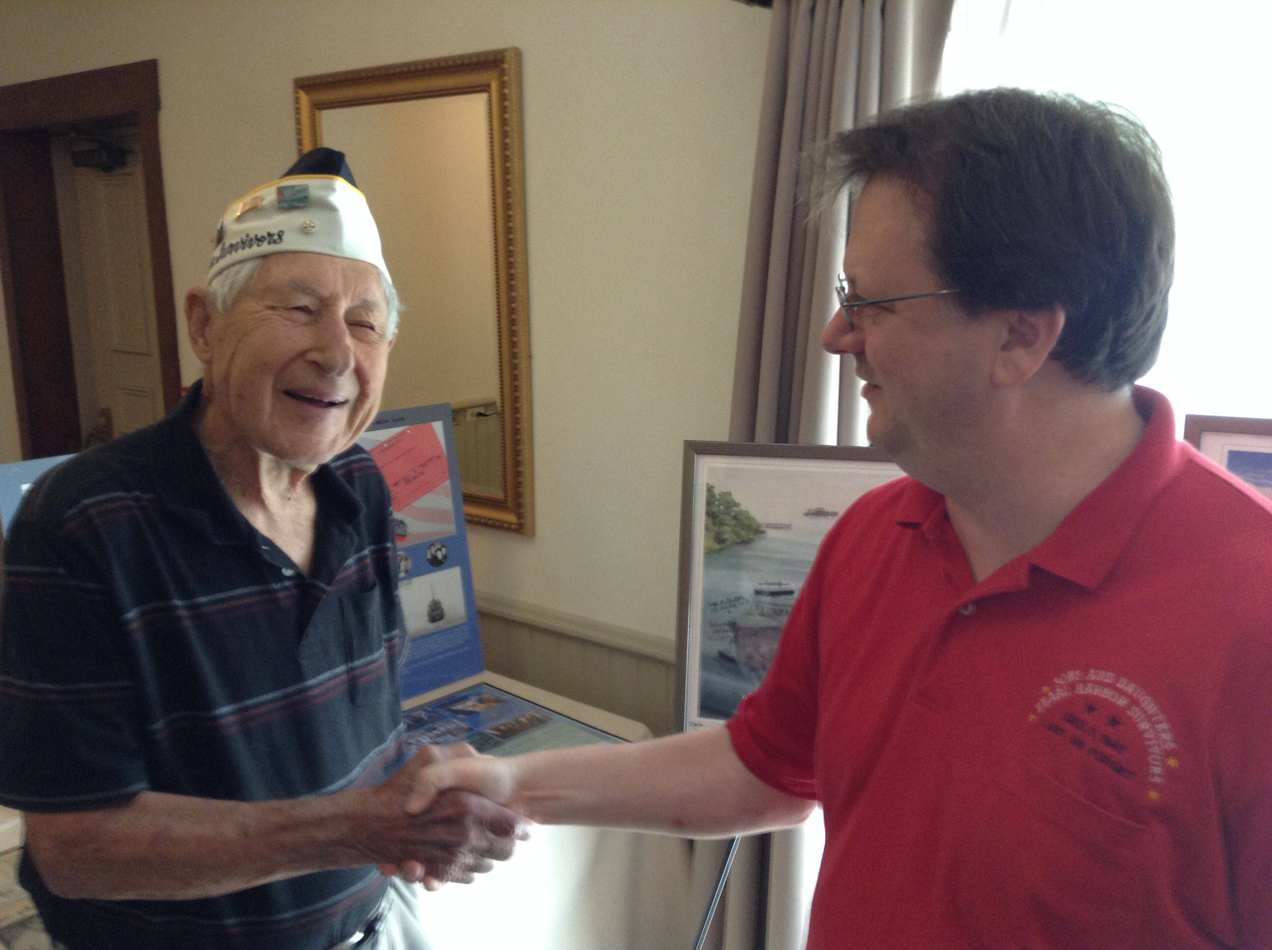 "Pearl Harbor survivor Lyle Hancock of Wheeling shakes hands with Eric ""Rick"" Miller on Sunday during the final meeting of Chapter One of the Pearl Harbor Survivors Association in Libertyville. Miller's late father was a member of the association."