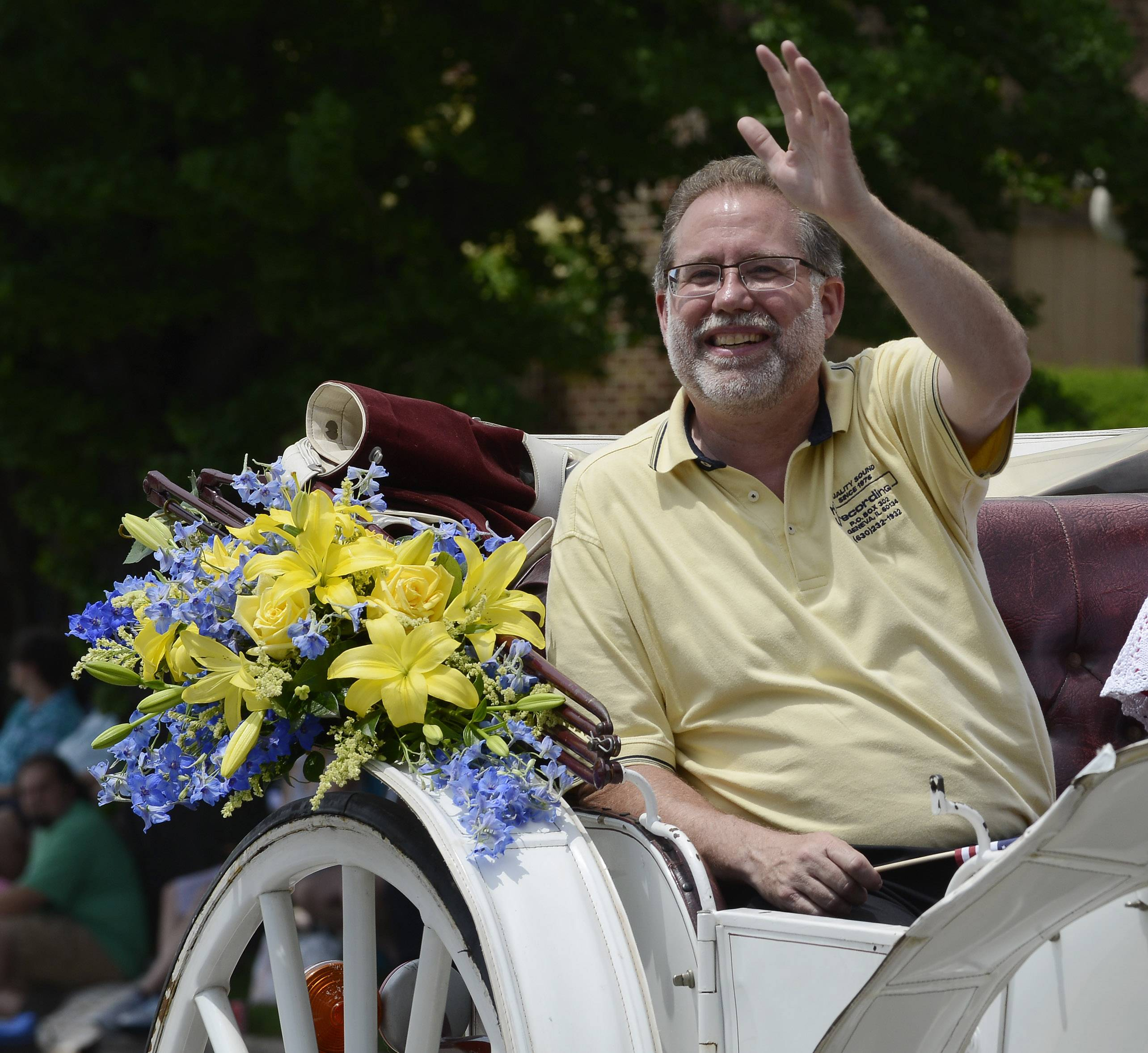 Parade Marshal Richard Peck waves to the crowd Sunday while riding in a horse-drawn carriage during the Swedish Days parade in downtown Geneva. This year was the 65th edition of the annual summer festival.