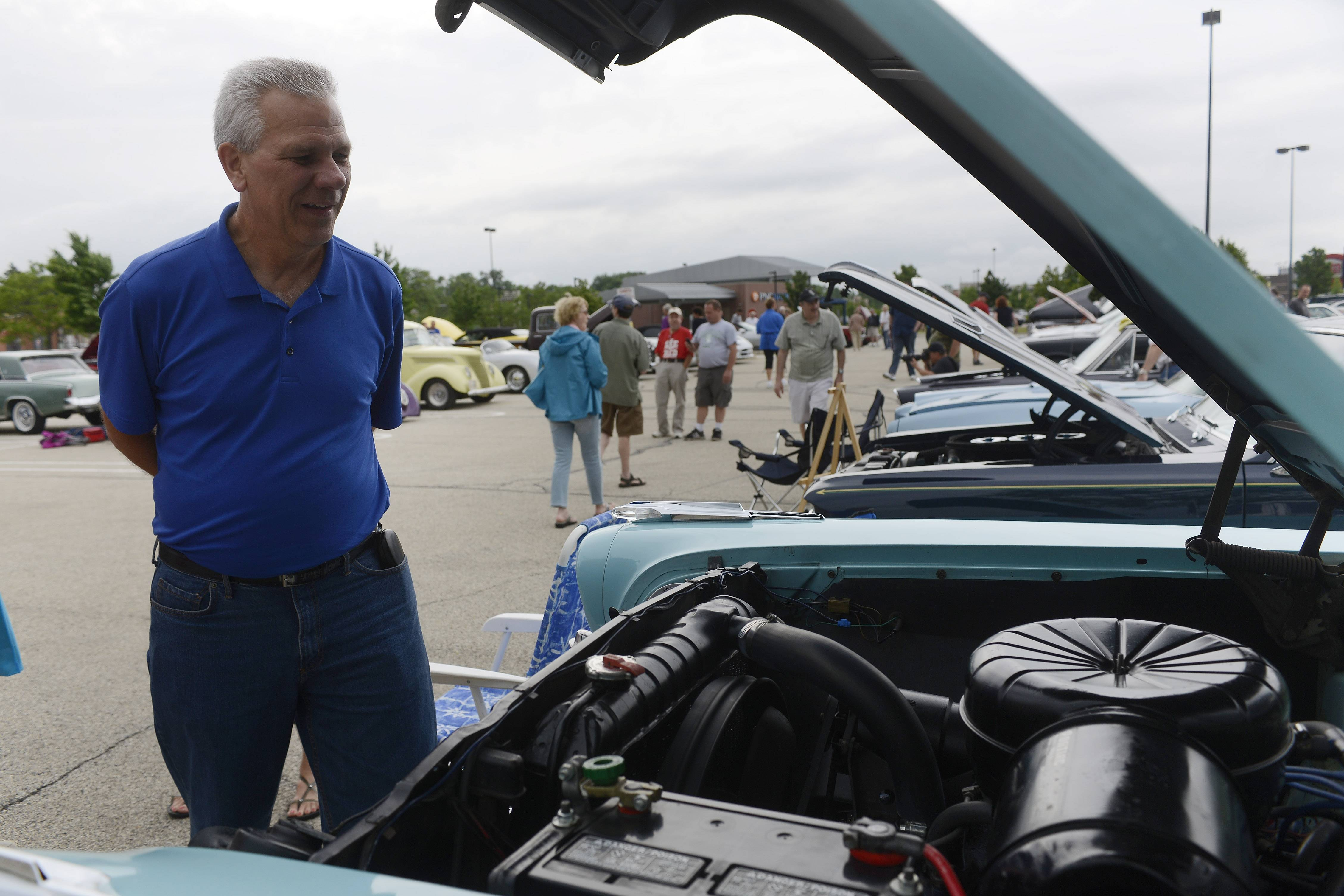 Tom Skipa of Arlington Heights views cars displayed during the Randhurst Village Cruise Night June 18 in Mount Prospect.