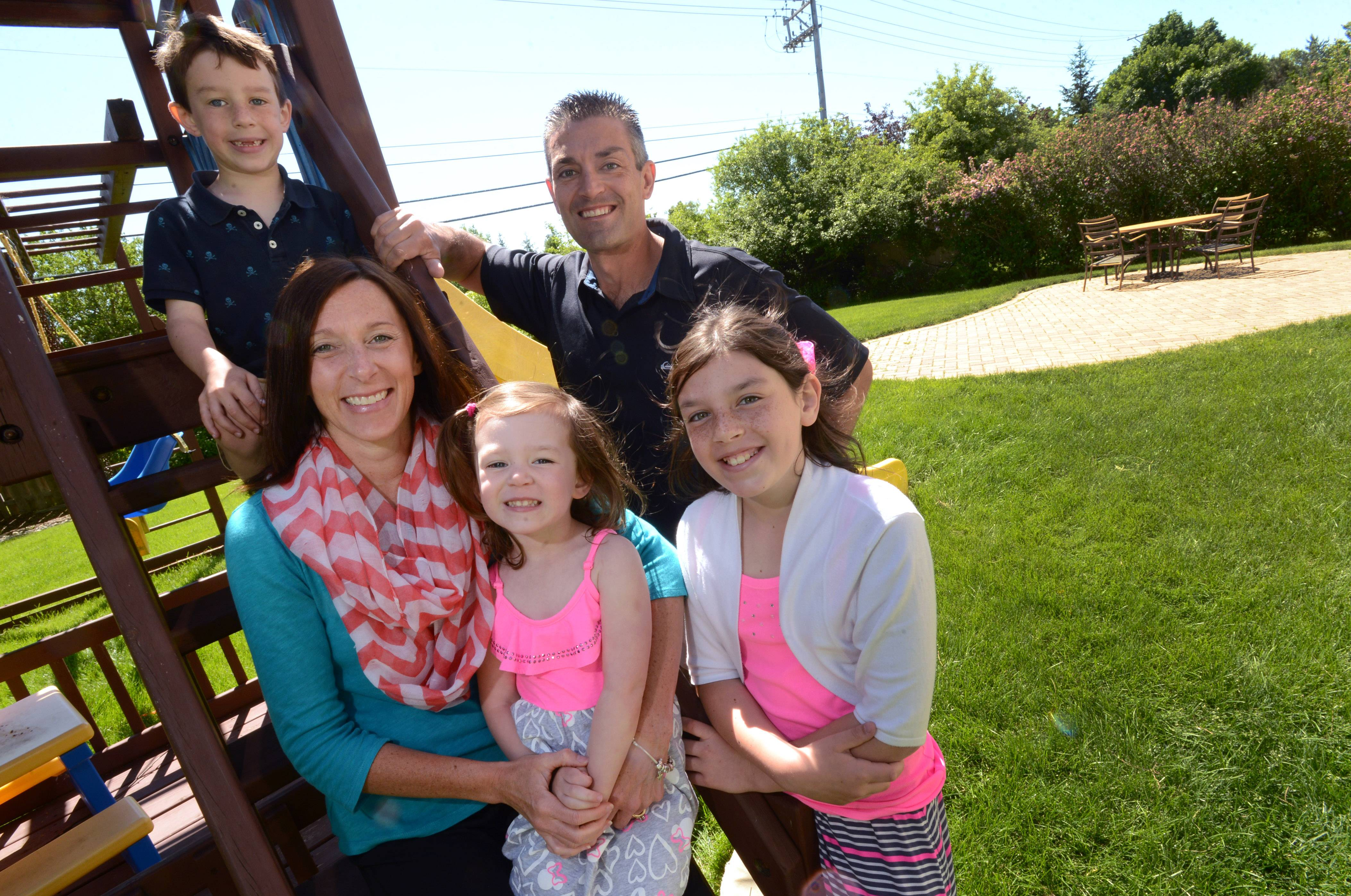 Jennifer and Jason Ness and their three children Max, 6, Lily, 3, and Samantha, 10, in their Lake Zurich backyard. They won the grand prize package in the Get Your Summer On contest and plan to get a new dining table with chairs, a grill and fire pit.