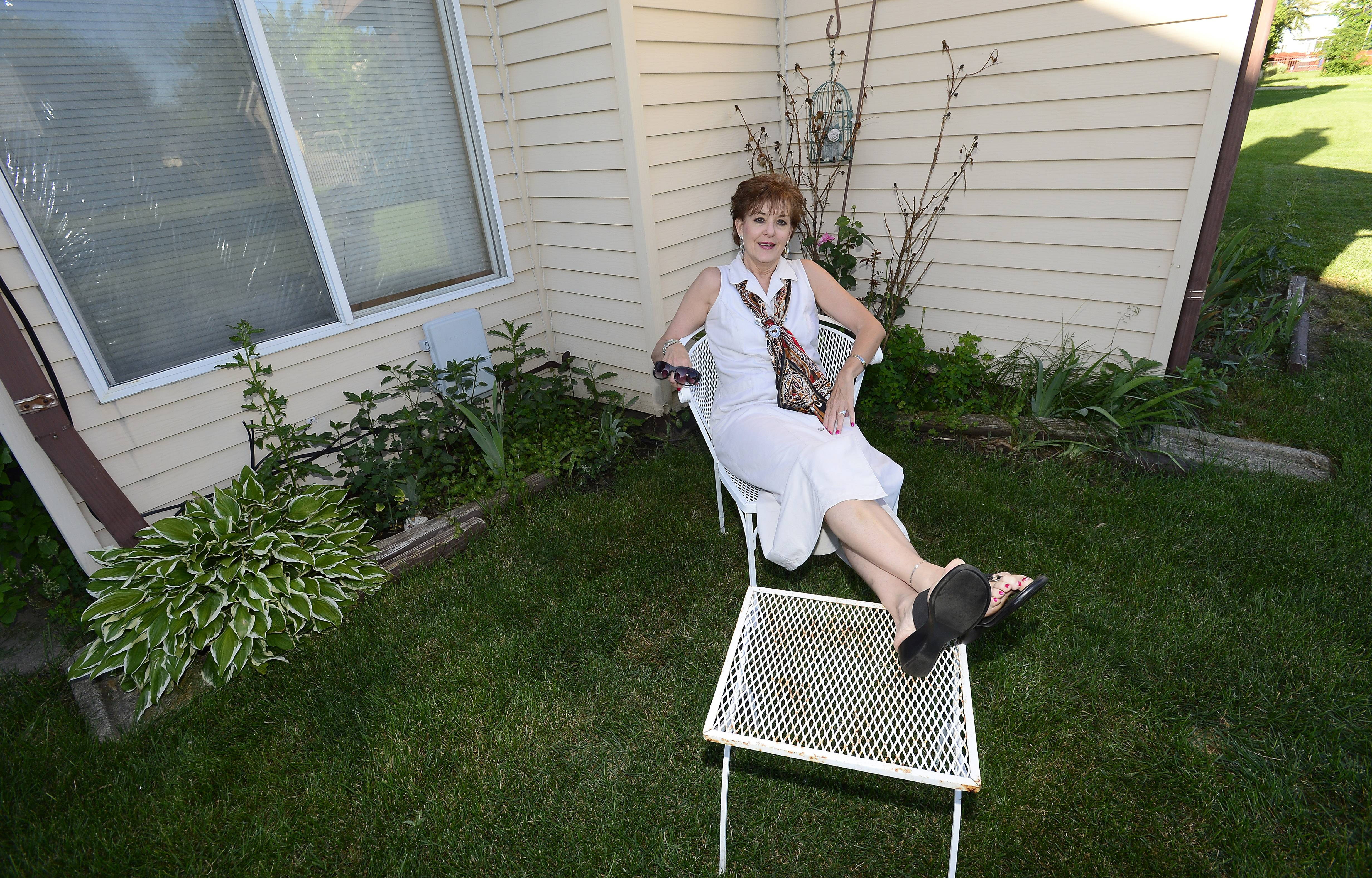 Kate Anderson of Hanover Park shows off her ugly backyard consisting of weeds, rotting beams and rusty patio furniture. Anderson won a $3,100 package including a Toro lawn mower and gift cards that will help her spuce up her landscaping and get some new furniture.