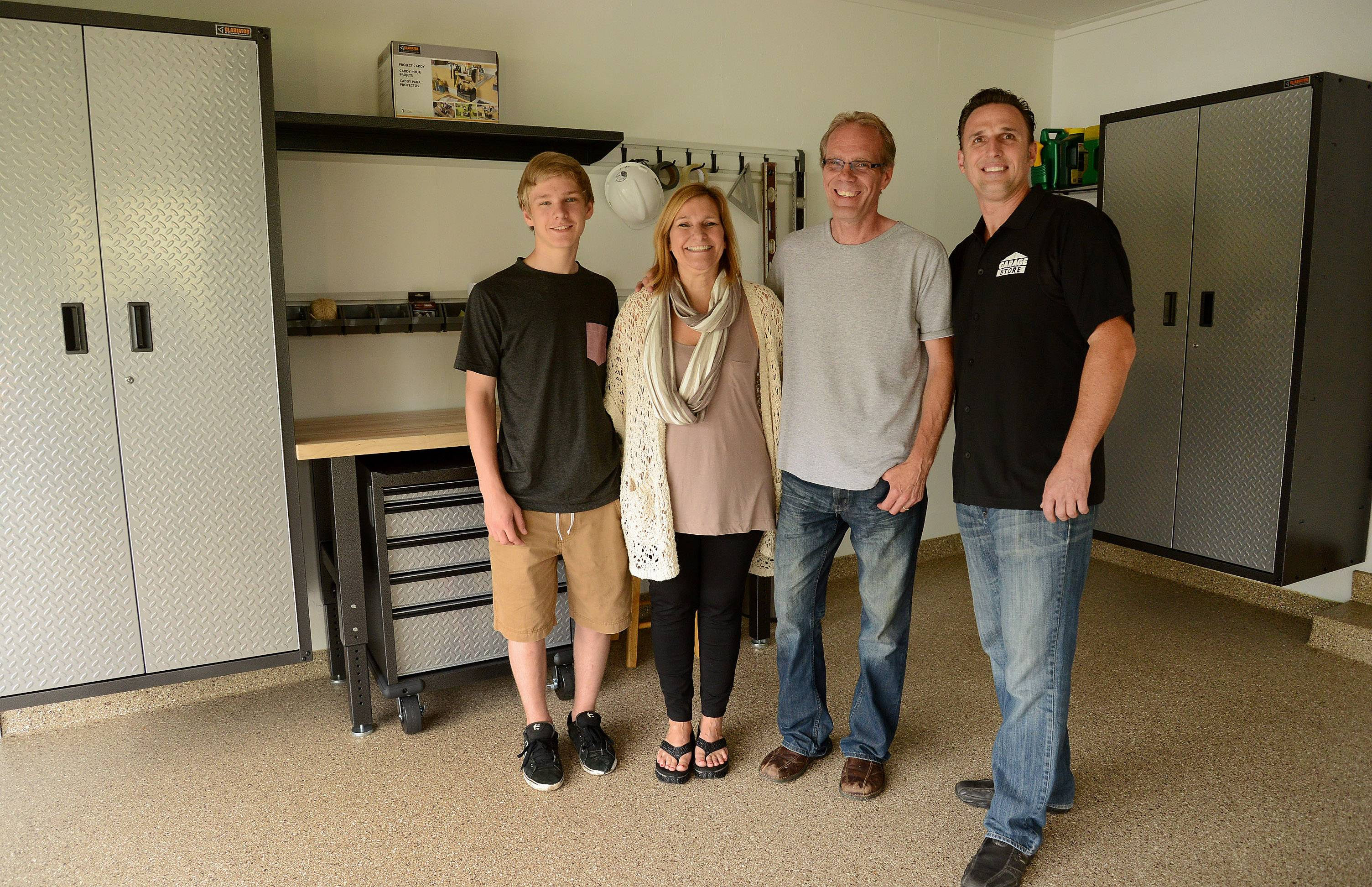 "Heidi Eglund of Prospect Heights, winner of the garage makeover contest, in her ""new"" garage with, from left, son Austin, husband Paul and Jim Melchert of Garage Store in East Dundee."