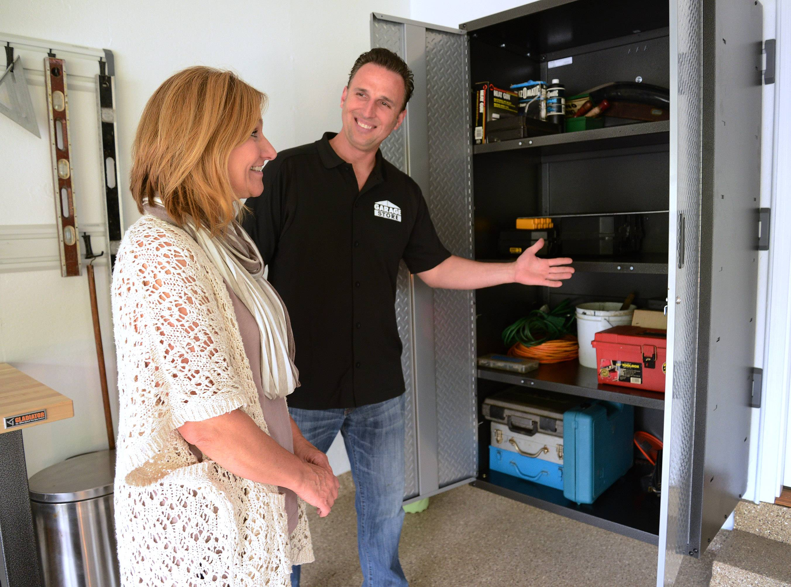 Jim Melchert of Garage Store in East Dundee shows Heidi Eglund of Prospect Heights, winner of a garage makeover contest, features of her new storage lockers.