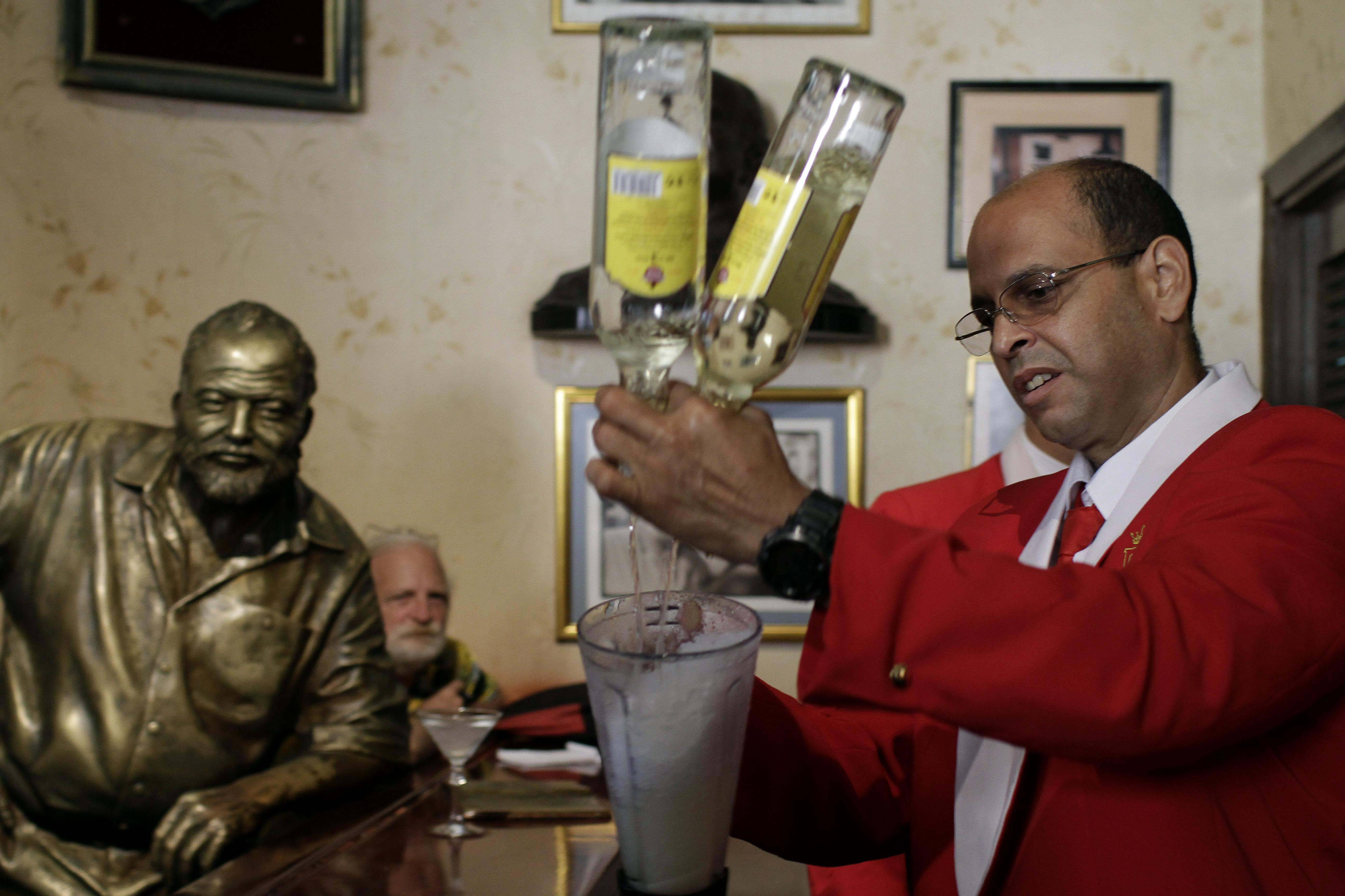 Bartender Alejandro Bolivar prepares a daiquiri at El Floridita tavern in Old Havana, Cuba, to honor the anniversary of the birth of its most famous frequent customer, novelist Ernest Hemingway, of whom a life-size sculpture sits bar side.