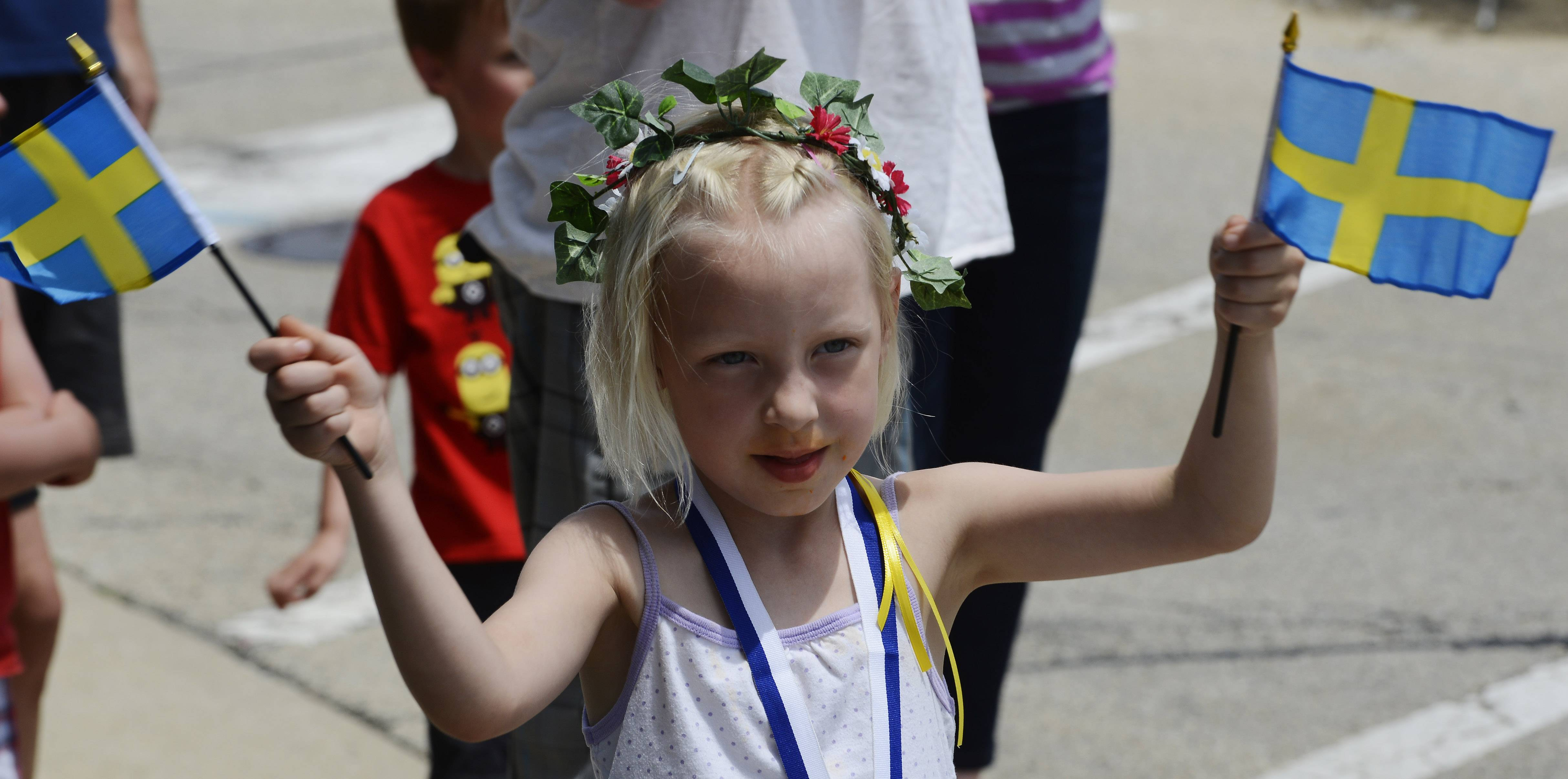 Kameko Cook, 5, of Addison, waves her Swedish flags Sunday during the Swedish Days parade in downtown Geneva. This year was the 65th edition of the annual summer festival.