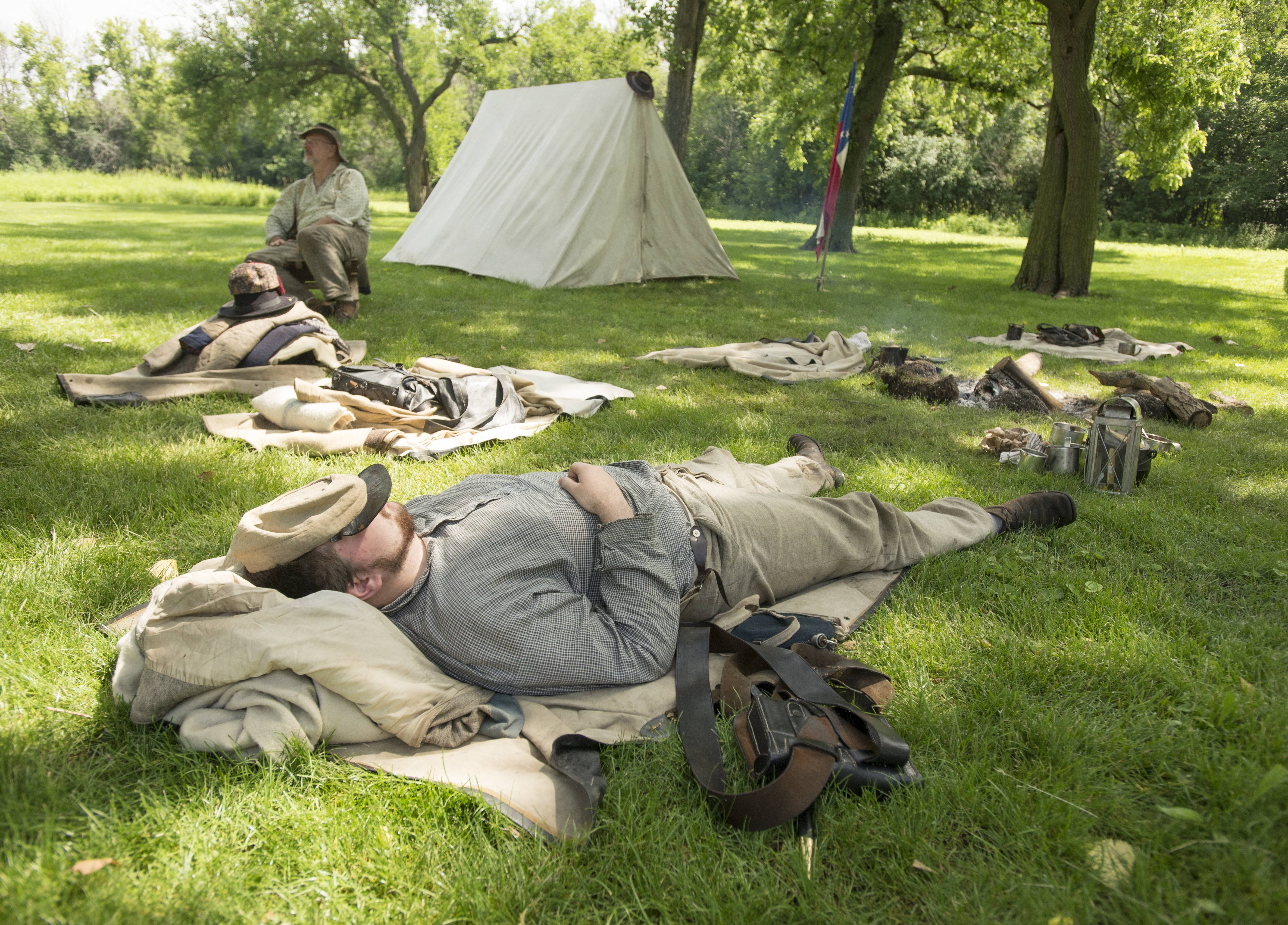 Jordan Smith of Sycamore, a Civil War re-enactor and member of Austin's Battalion Louisiana Sharp Shooters, rests while portraying camp life Sunday during a Civil War re-enactment at Fischer Farm in Bensenville. This was the second year the farm has hosted a Civil War Days event.