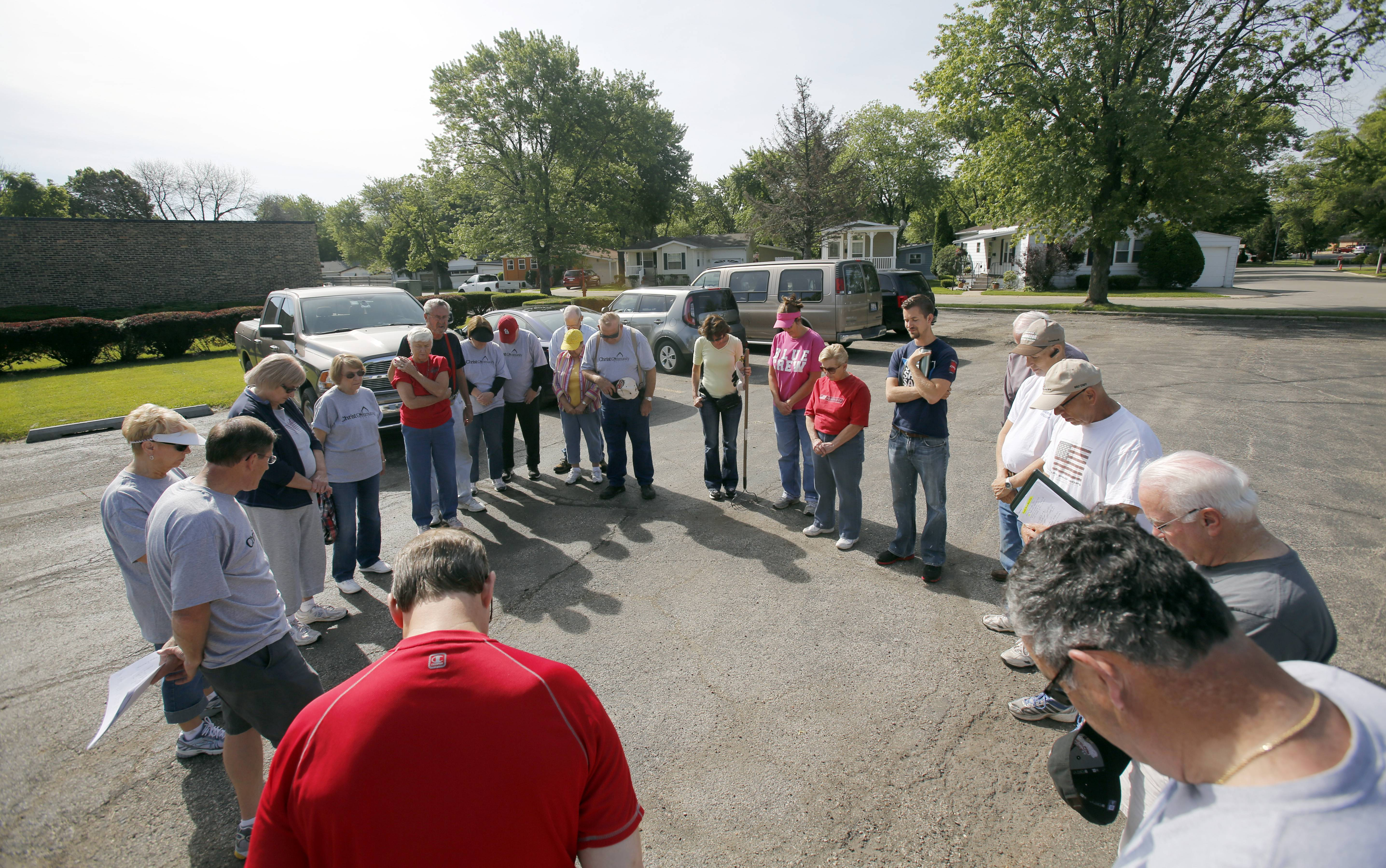 A group from Christ Community Church in St. Charles prays in the parking lot before heading out to help people in Willow Lake Estates in Elgin.