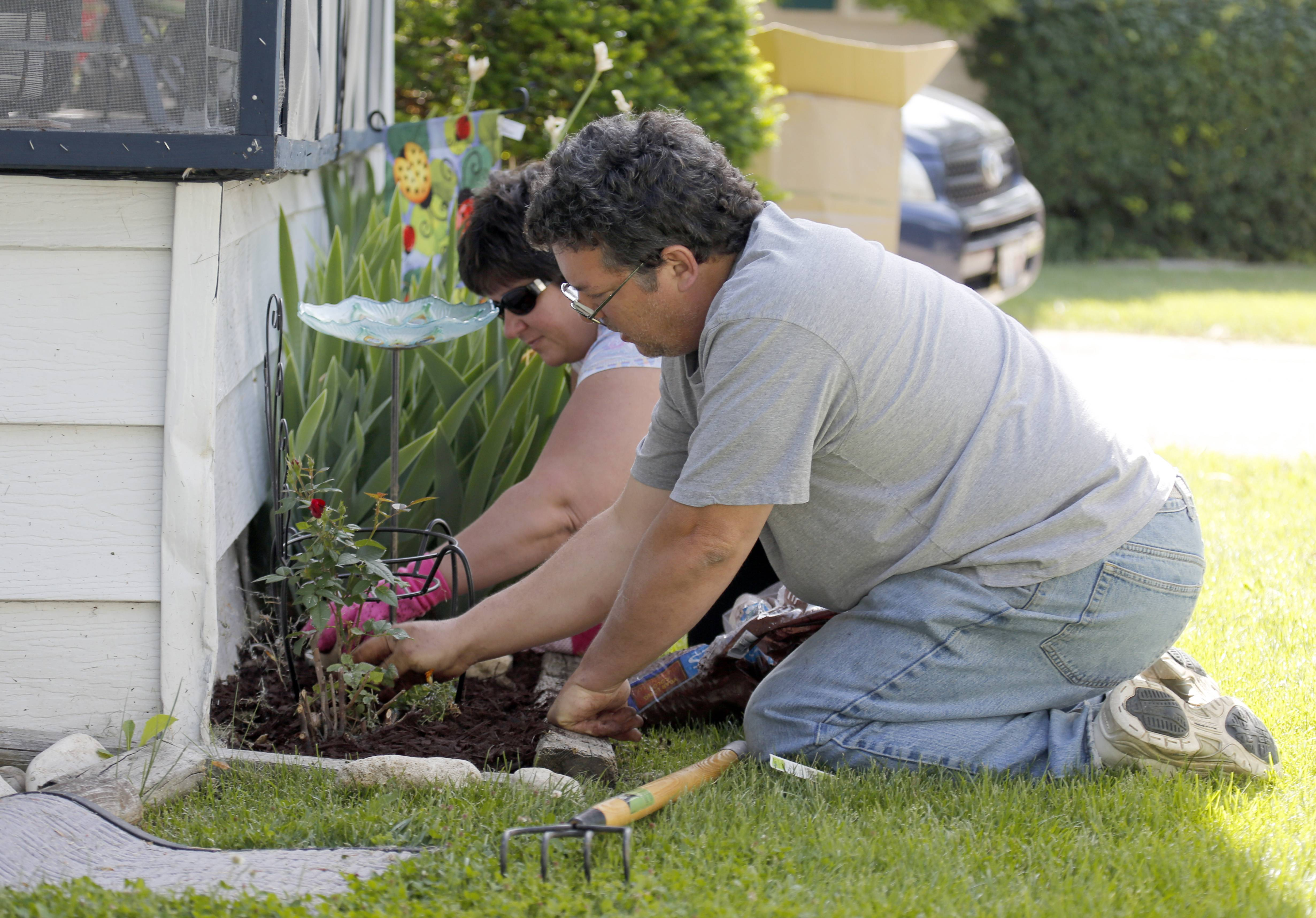 Dean and Tammy Matthews of Christ Community Church in St. Charles work on weeding a Willow Lake Estates resident's garden.