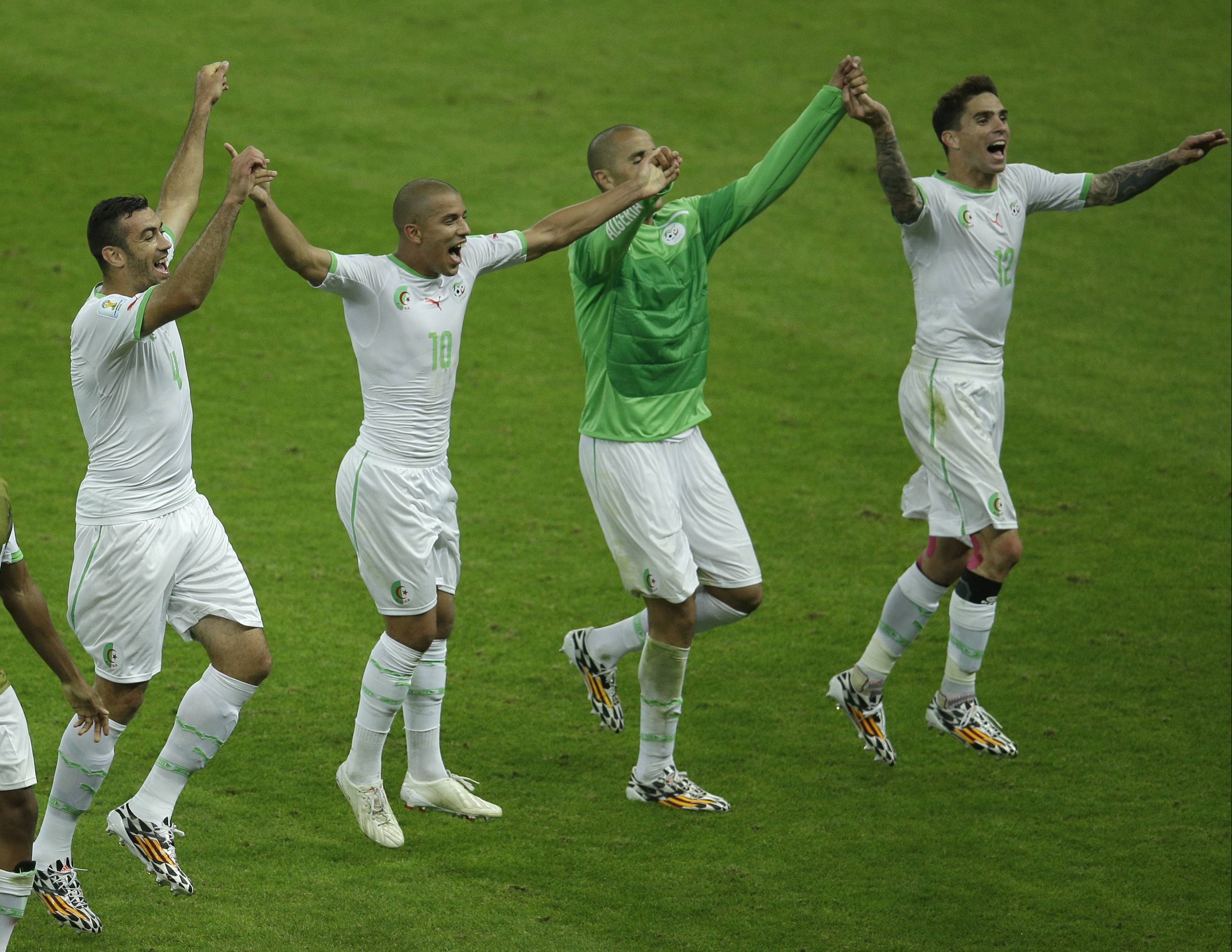 Members of the Algerian soccer team join hands as they celebrate after winning 4-2, the group H World Cup soccer match between South Korea and Algeria at the Estadio Beira-Rio in Porto Alegre, Brazil, Sunday, June 22, 2014.