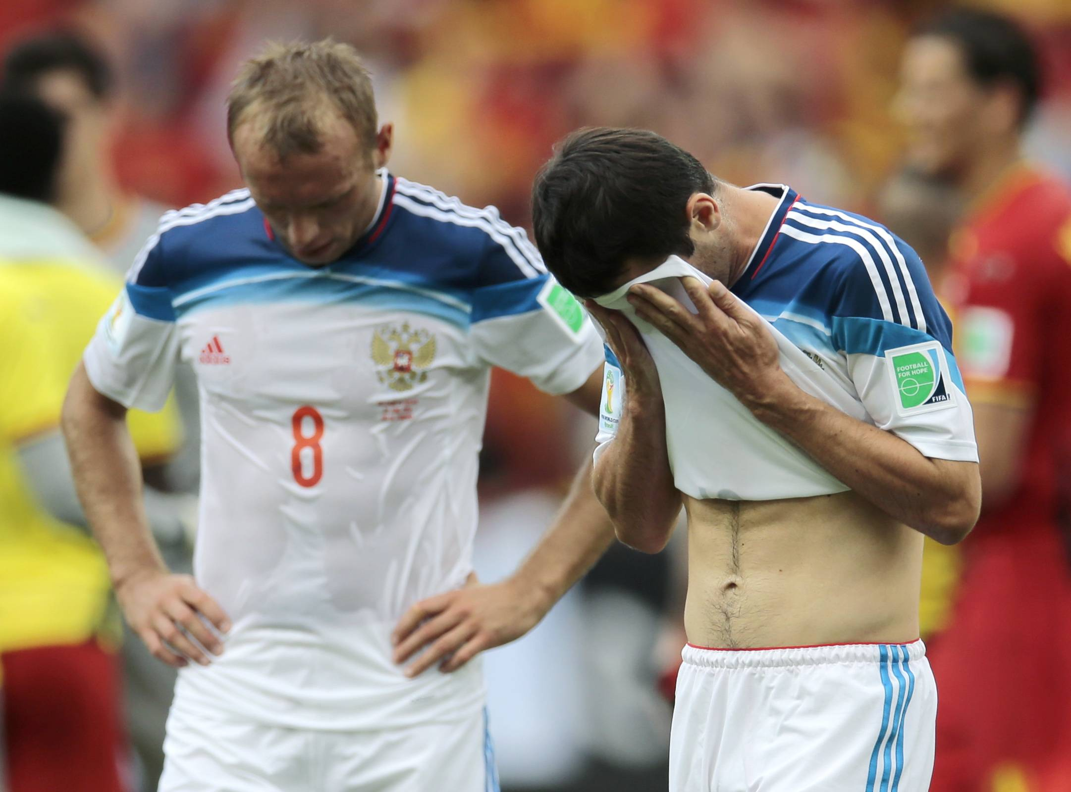 Russia's Denis Glushakov, left, and Russia's Alan Dzagoev react after the group H World Cup soccer match between Belgium and Russia at the Maracana Stadium in Rio de Janeiro, Brazil, Sunday, June 22, 2014. Belgium won the match 1-0.