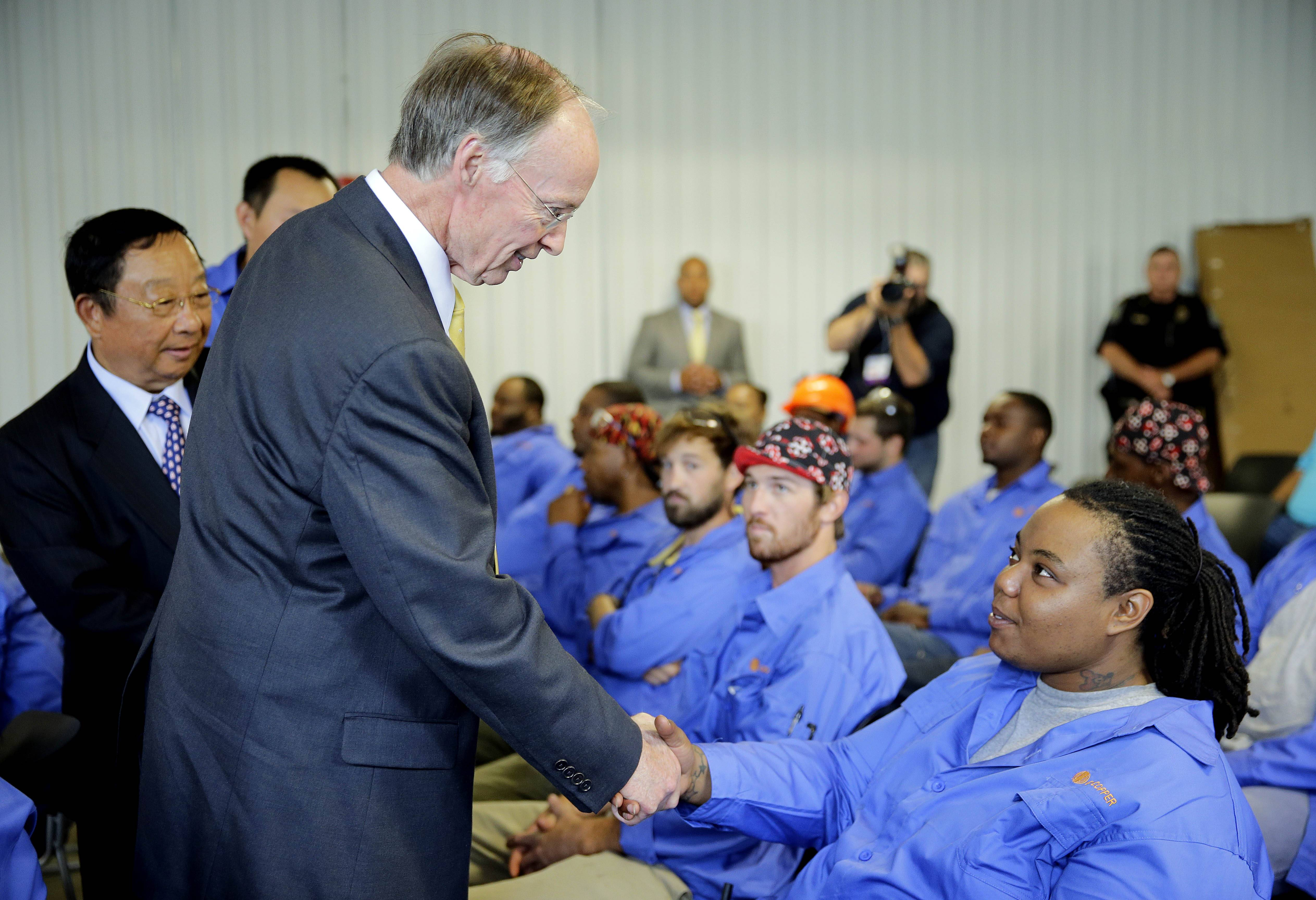 Alabama Gov. Robert Bentley, followed by Golden Dragon Copper USA Chairman Changjie Li, left, meets the employees of Golden Dragon Copper USA before the company's grand opening ceremony in Pine Hill, Ala. Golden Dragon, the first company Bentley recruited to Alabama after being elected, will employ 300 new full-time employees in rural Wilcox County.