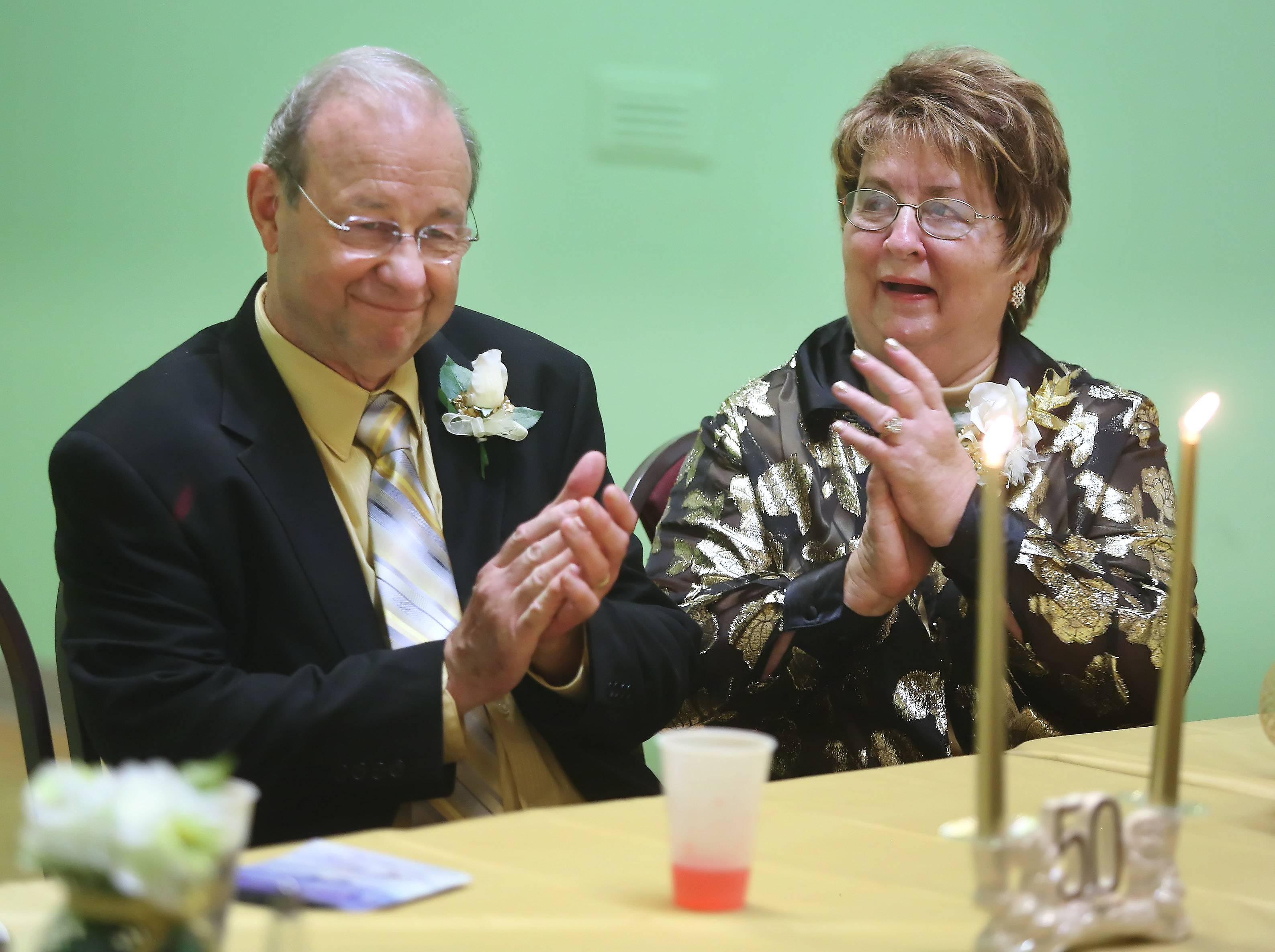 Marilyn and Warren Sunderlage clap after a speech was made in their honor during their 50th anniversary celebration Sunday at the Vogelei Barn in Hoffman Estates. Warren is the great-great grandson on Johann Sunderlage, the first settler of Schaumburg Township, and their family holds a significant place in Hoffman Estates history.