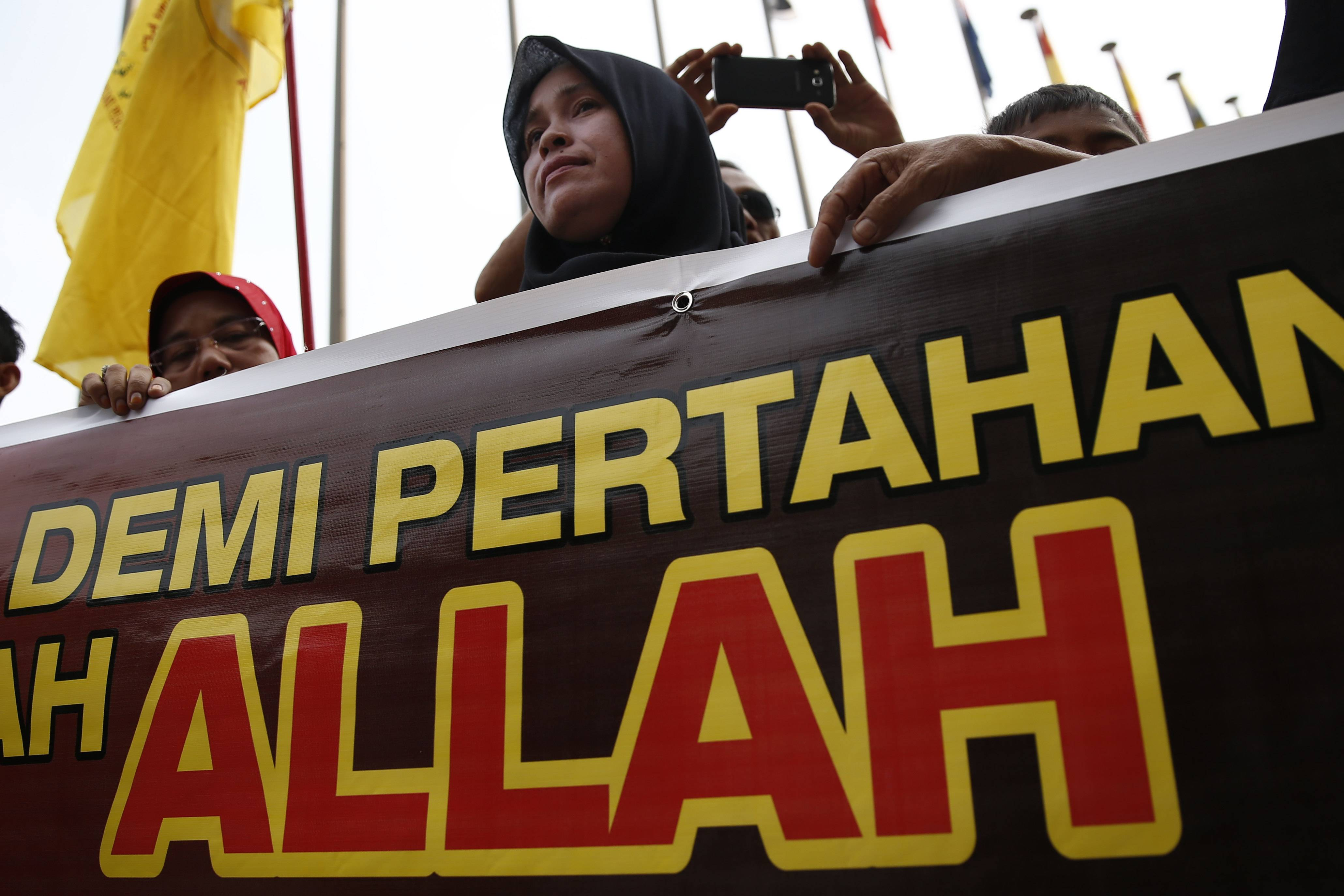 "A Muslim woman holds a banner reading ""Allah"" Monday during a protest outside the Court of Appeal in Putrajaya, outside Kuala Lumpur, Malaysia. The Federal Court on Monday refused to grant leave to hear the appeal by the Catholic church over the word Allah in its newspaper."