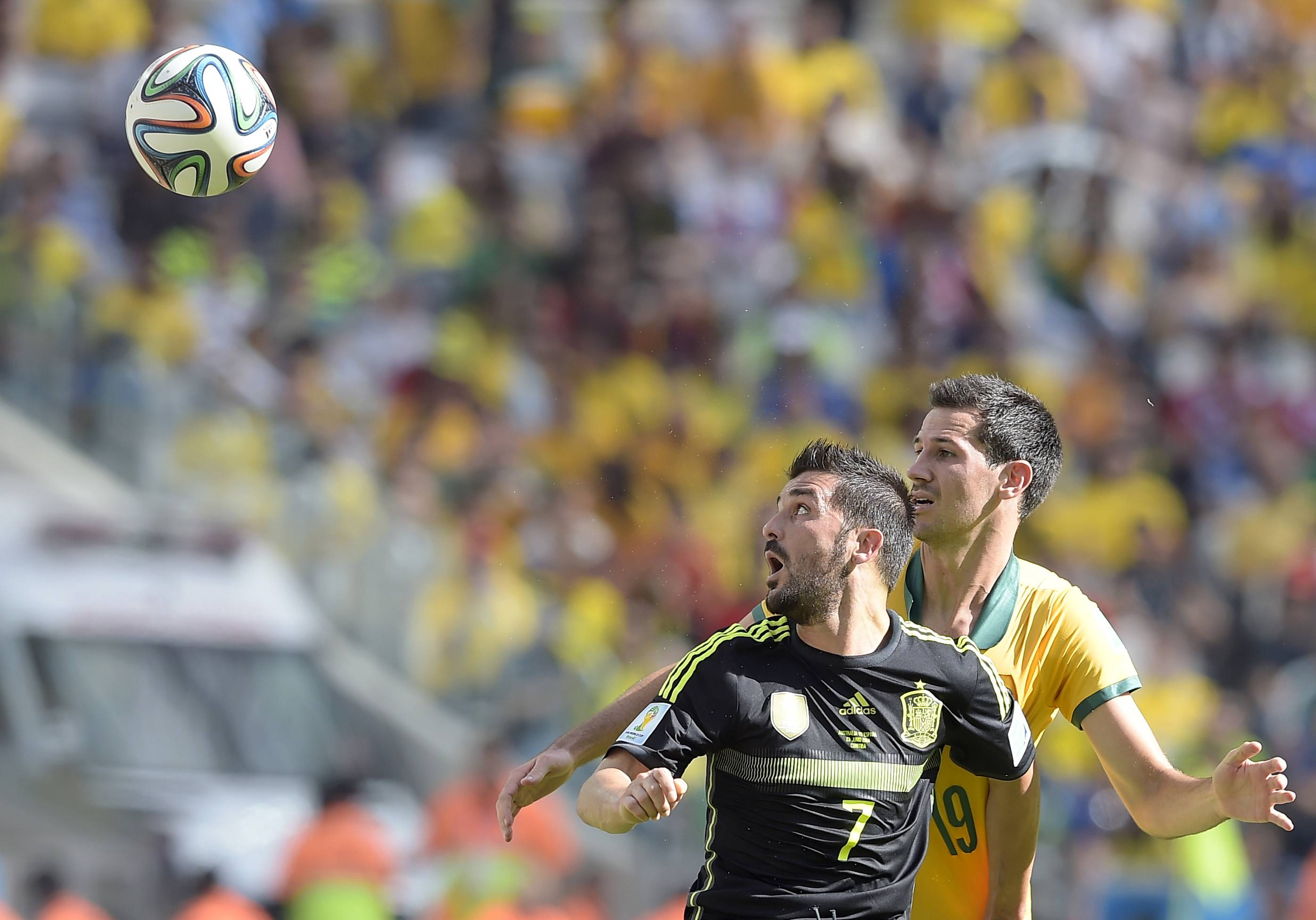 Spain's David Villa, left, and Australia's Ryan McGowan go for a header Monday during a Group B World Cup soccer match at the Arena da Baixada in Curitiba, Brazil.