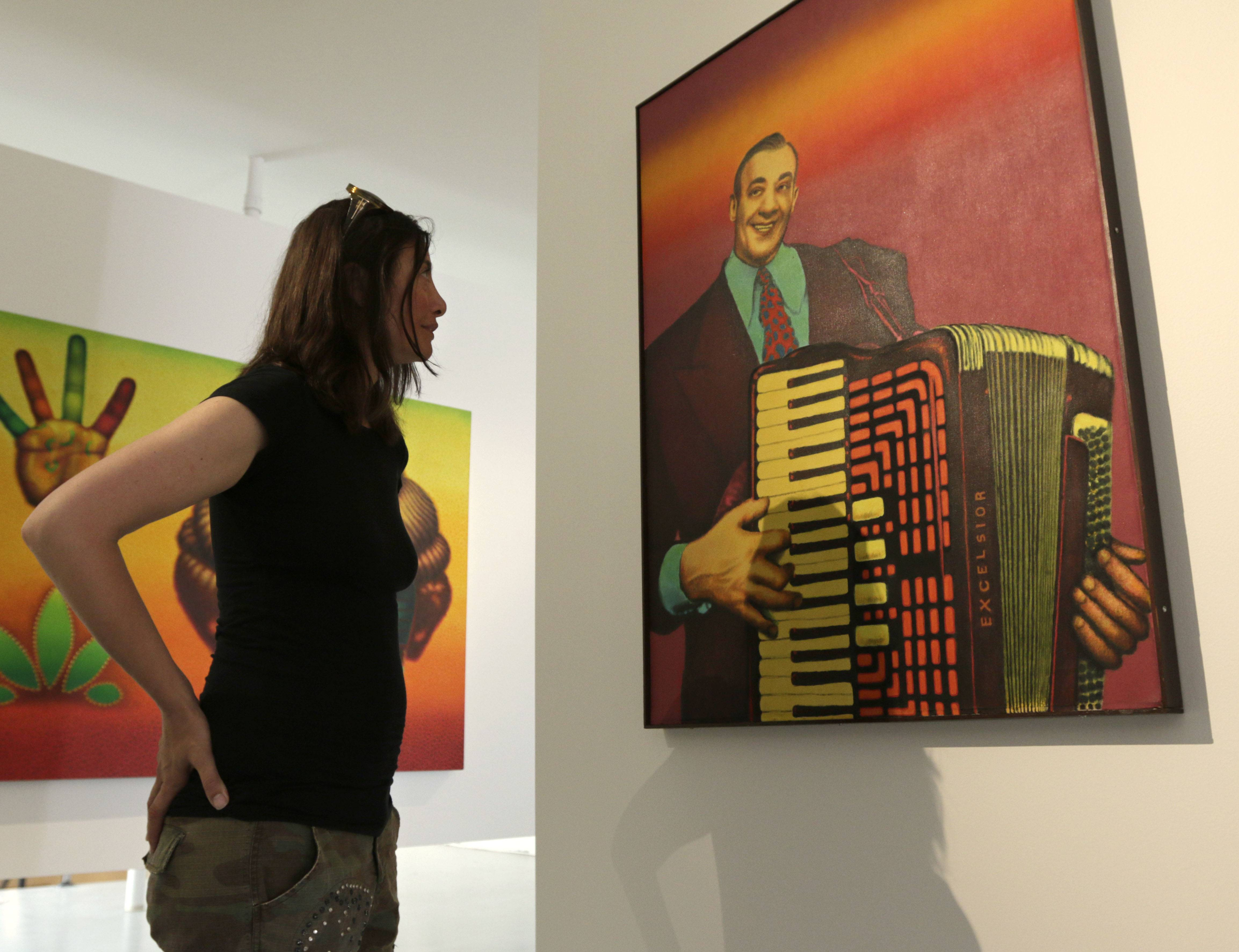 "Vesna K. Stelcer, board chair of the Ed Paschke Foundation, looks at an Ed Paschke painting titled ""Accordian Man"" that's on display at the Ed Paschke Art Center."