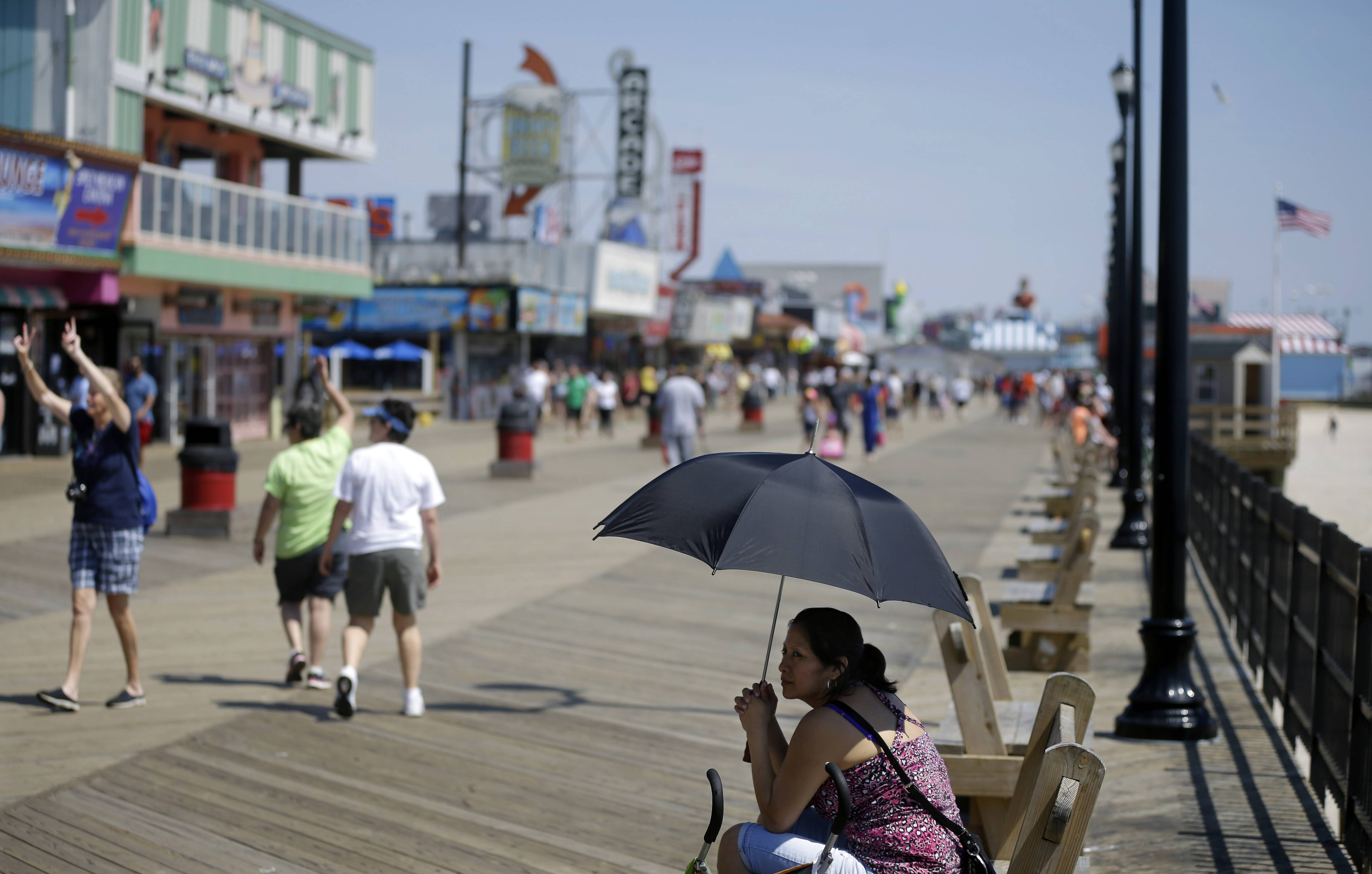 A woman seeks shade under an umbrella along the boardwalk on Memorial Day in Seaside Heights, N.J. There's no better place to engage in people-watching than on the boardwalks of the Jersey shore, and almost all of them are rebuilt and good as new in the second summer after Superstorm Sandy.
