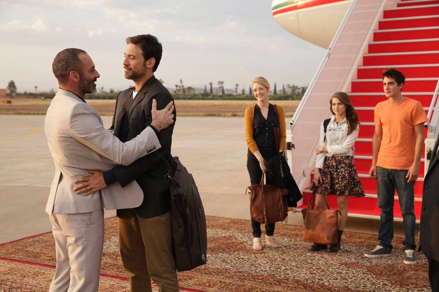 "Jamal (Ashraf Barhom), left, welcomes his brother Barry (Adam Rayner) back to their strife-filled Middle Eastern homeland in FX's new drama ""Tyrant."" Accompanying Barry are his American wife (Jennifer Finnegan) and children (Anne Winters and Noah Silver)."